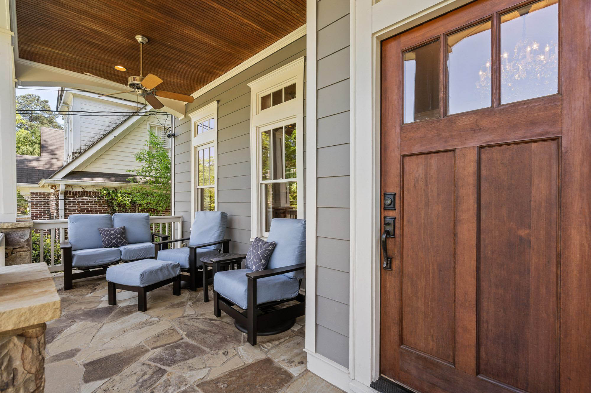 front porch design with black chairs & blue cushions. Stone floor and columns, wood front door, gray siding