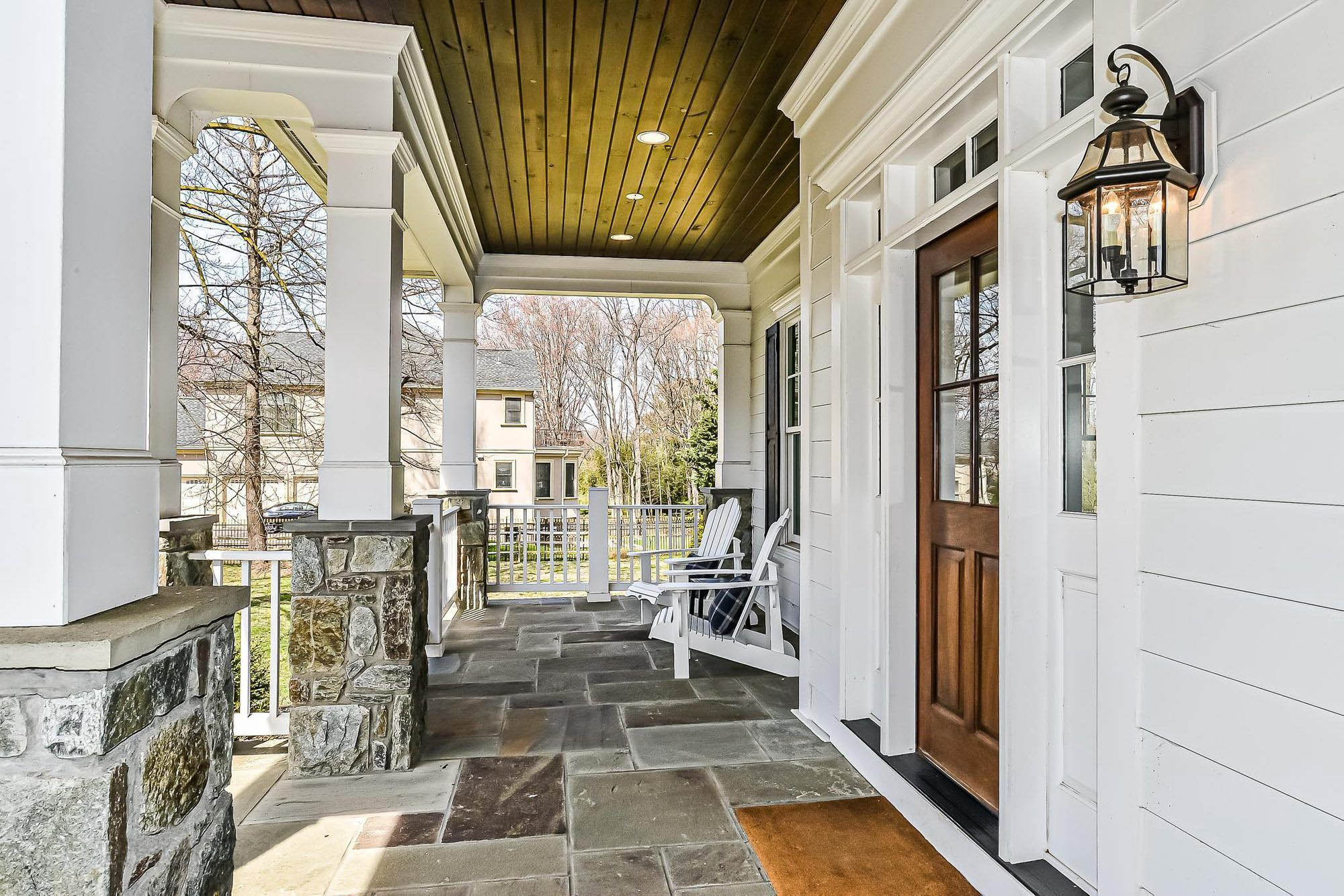 covered front porch with real stone porch top and stone columns wood front door wood ceiling.