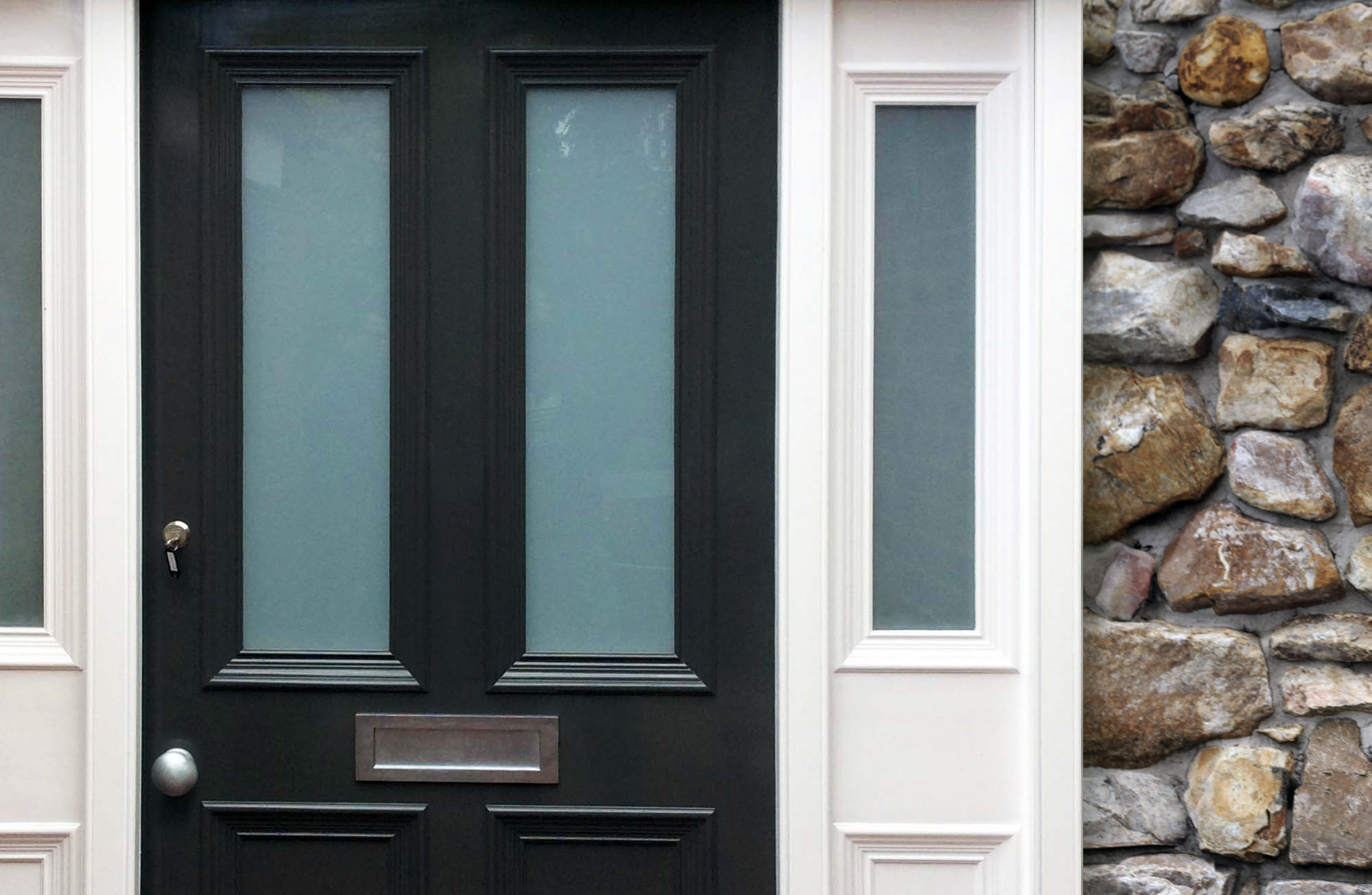 Beautiful dark gray front door with mail slot, transoms, white trim and pale earthy stone veneer. Brushed hardware.