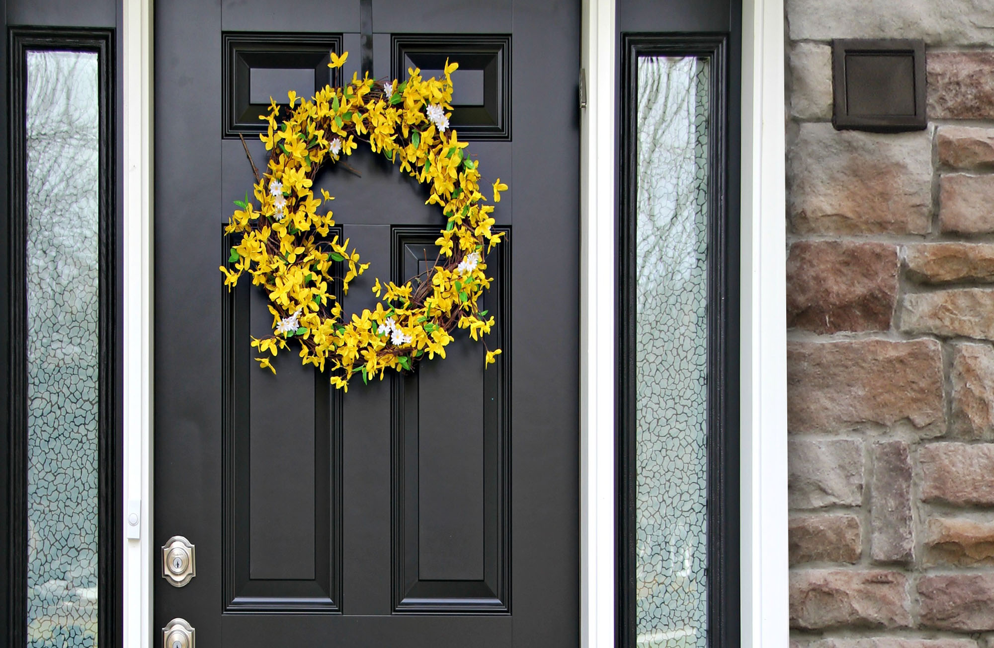 black front door with sidelights, white rim and brown stone veneer, yellow flower wreath