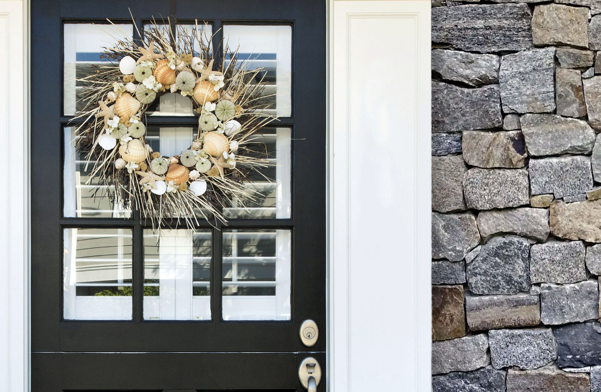black front door with wreath stone veneer siding thick white trim glass