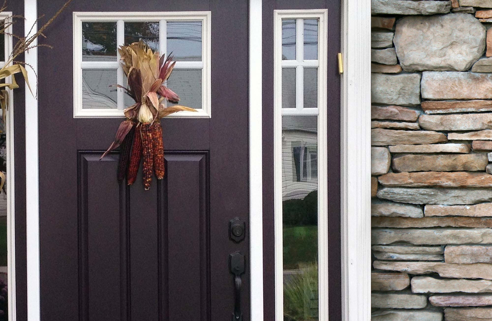 purple front door with gray stone veneer siding, white trim, black hardware, fall decoration on the door.