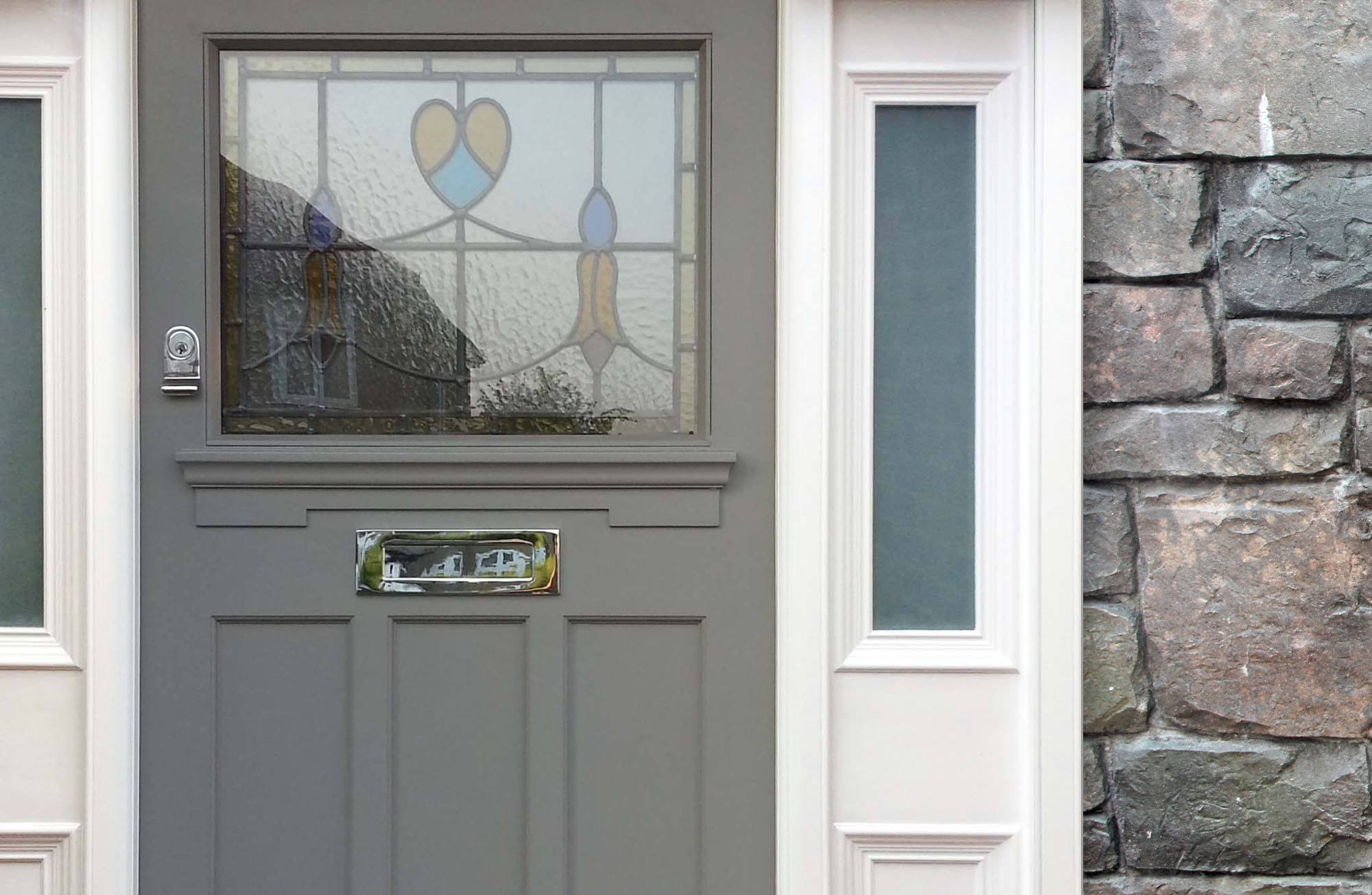 slate gray fron door with stained glass white trim and gray stone veneer