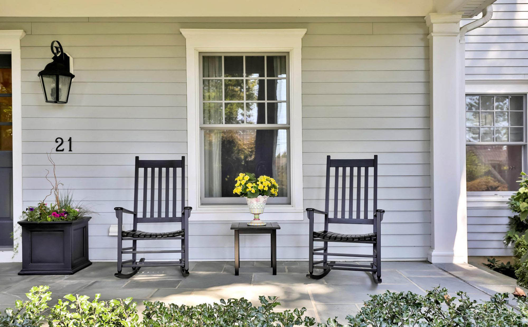cheap patio furniture ideas. Simple outdoor black rocking chairs, table and planters. Porch plants.