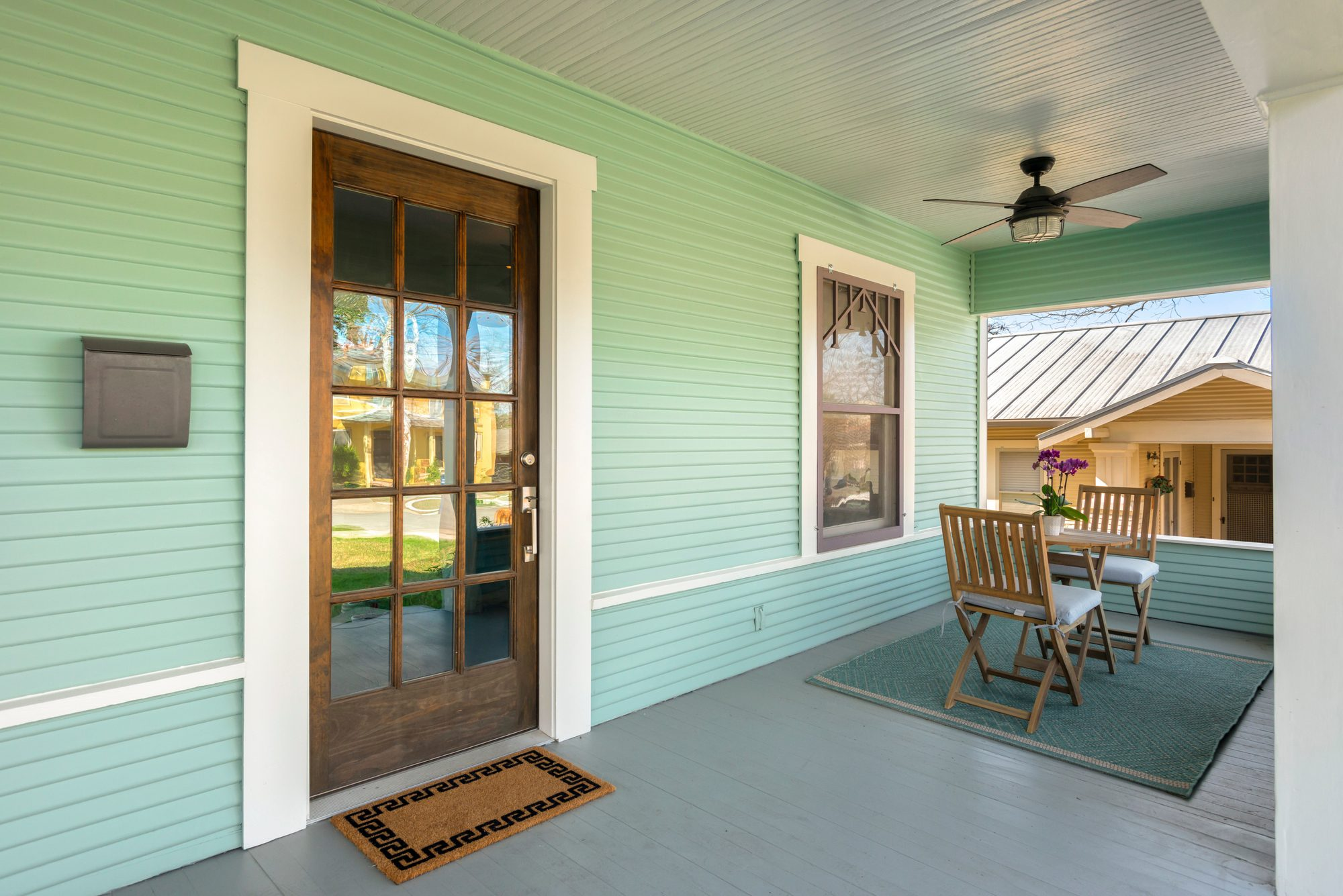 pastel green siding wood door with glass white trim simple table and chairs front porch design