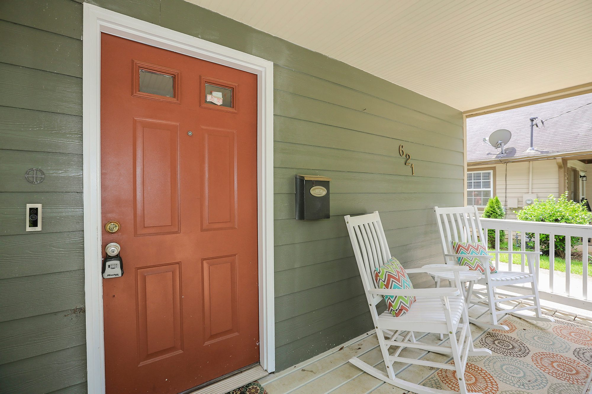 simple covered front porch orange front door green siding white rocking chairs