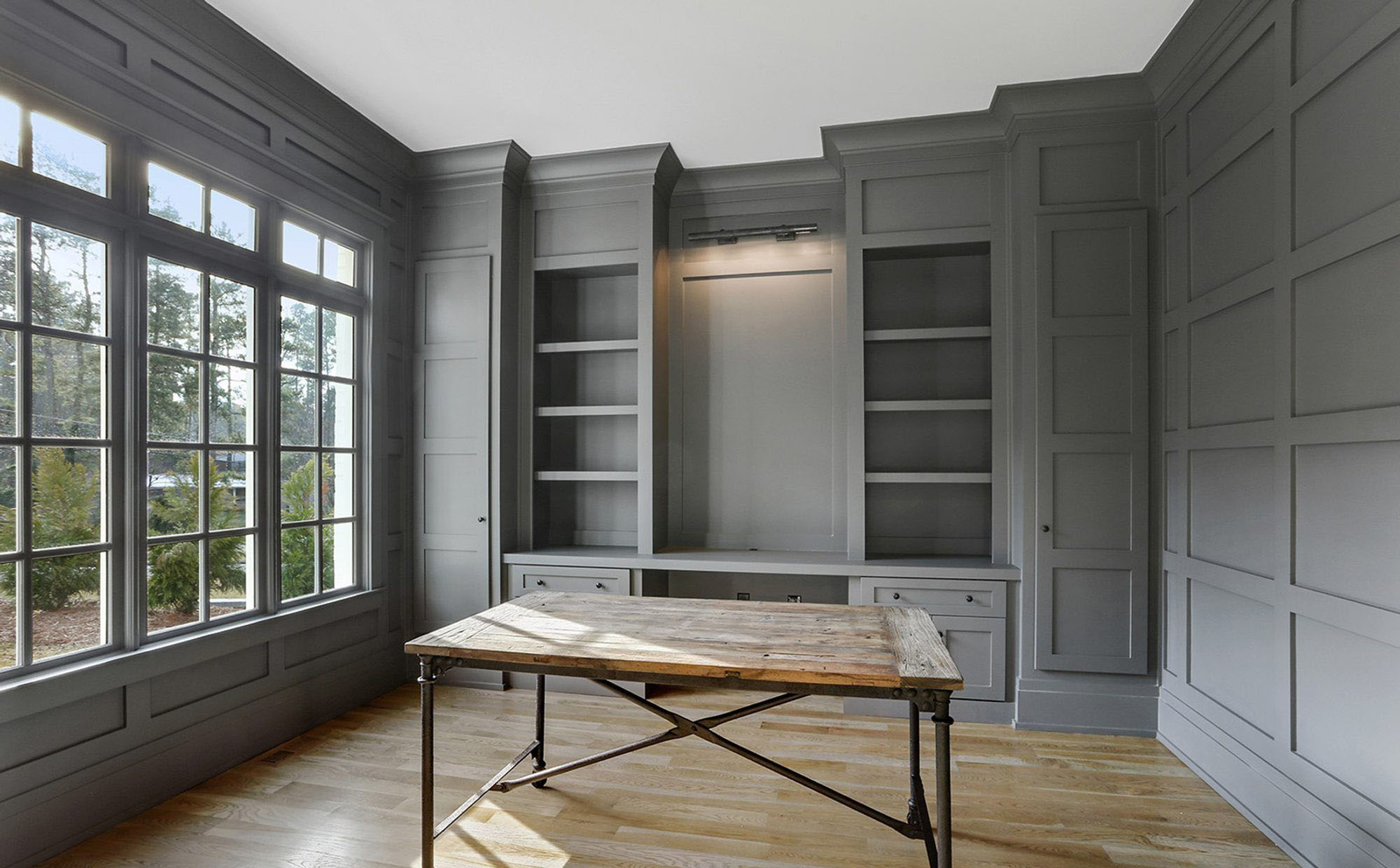 gray monochromatic office color scheme with built ins and wall paneling, wood floors and rustic desk