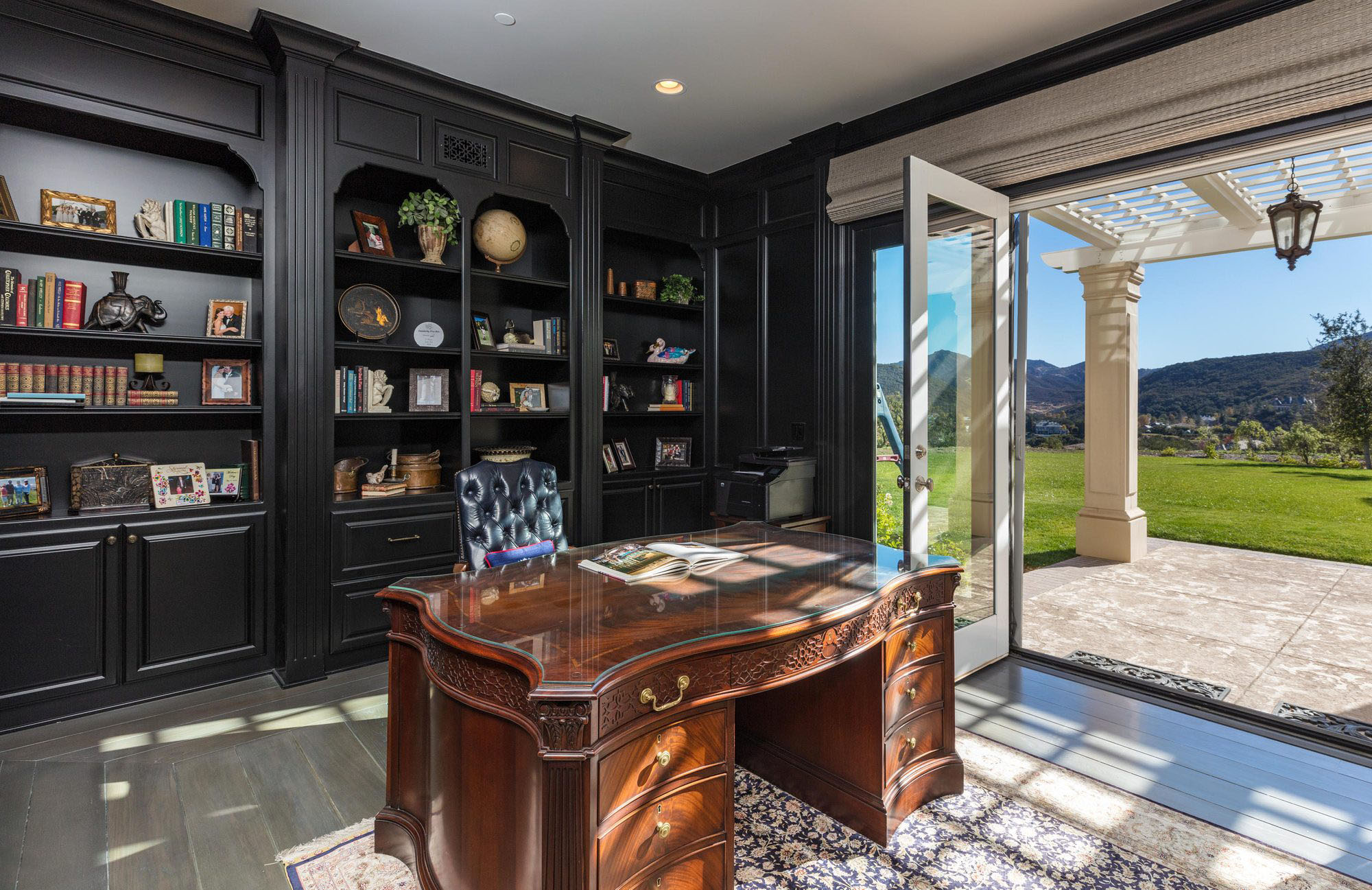 black monochromatic home office black built in shelves and wall pant folding doors indoor outdoor design large wood desk