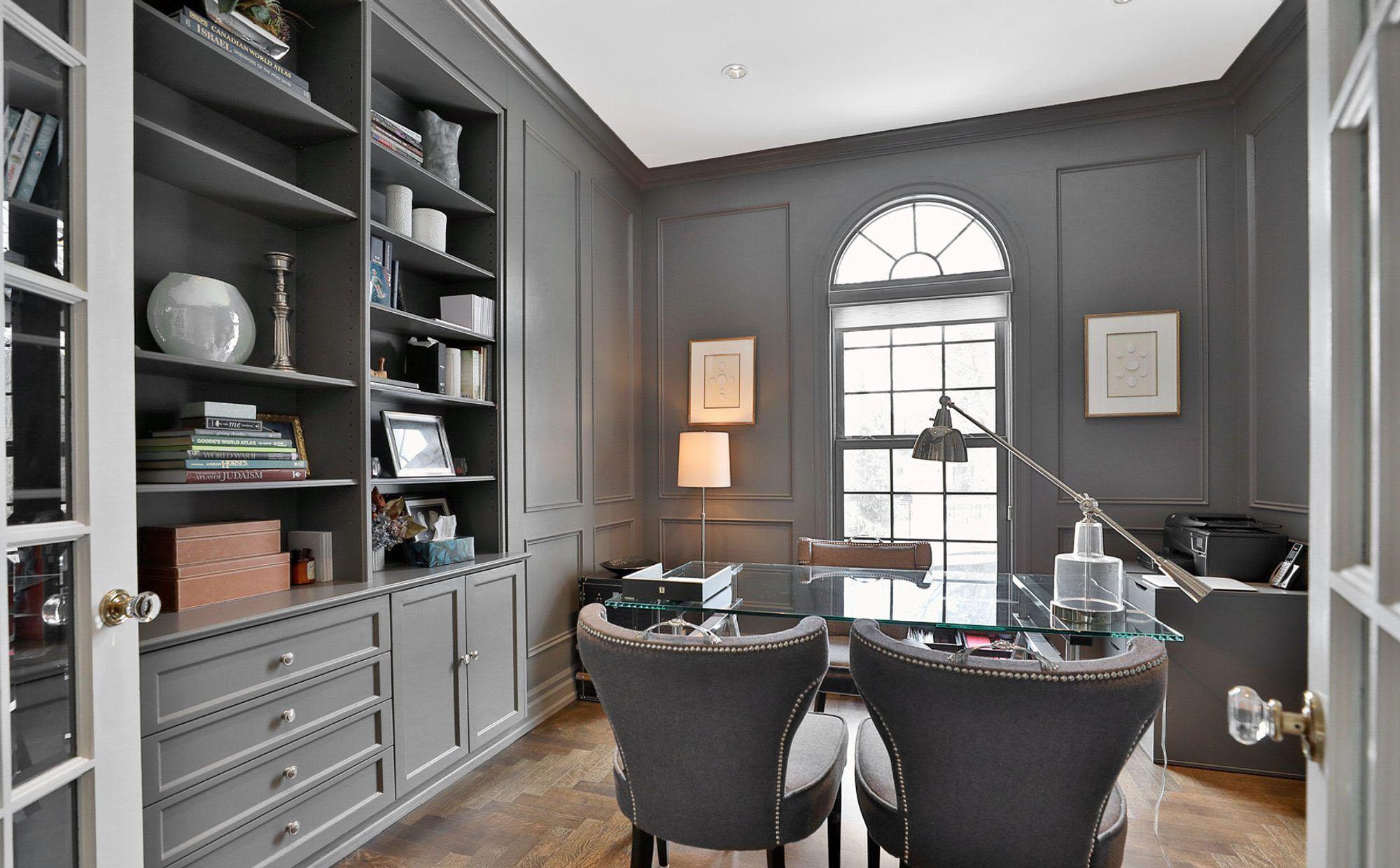 Monochromatic office with a medium gray color scheme. wood floors. glass desk.