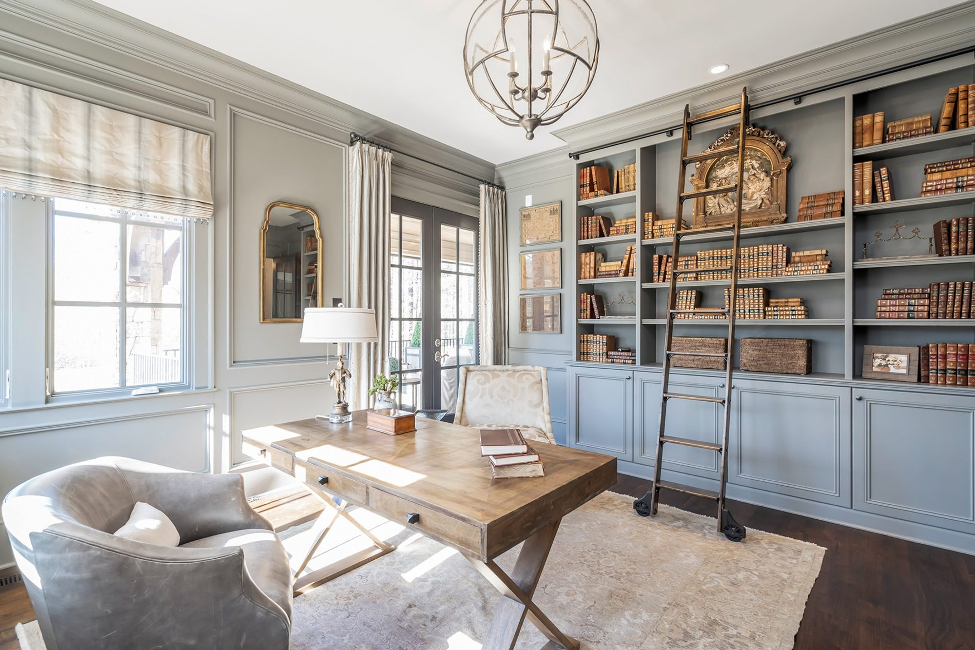light gray monochromatic color scheme office with built ins cabinets and shelving dark wood floors, rug, light wood desk