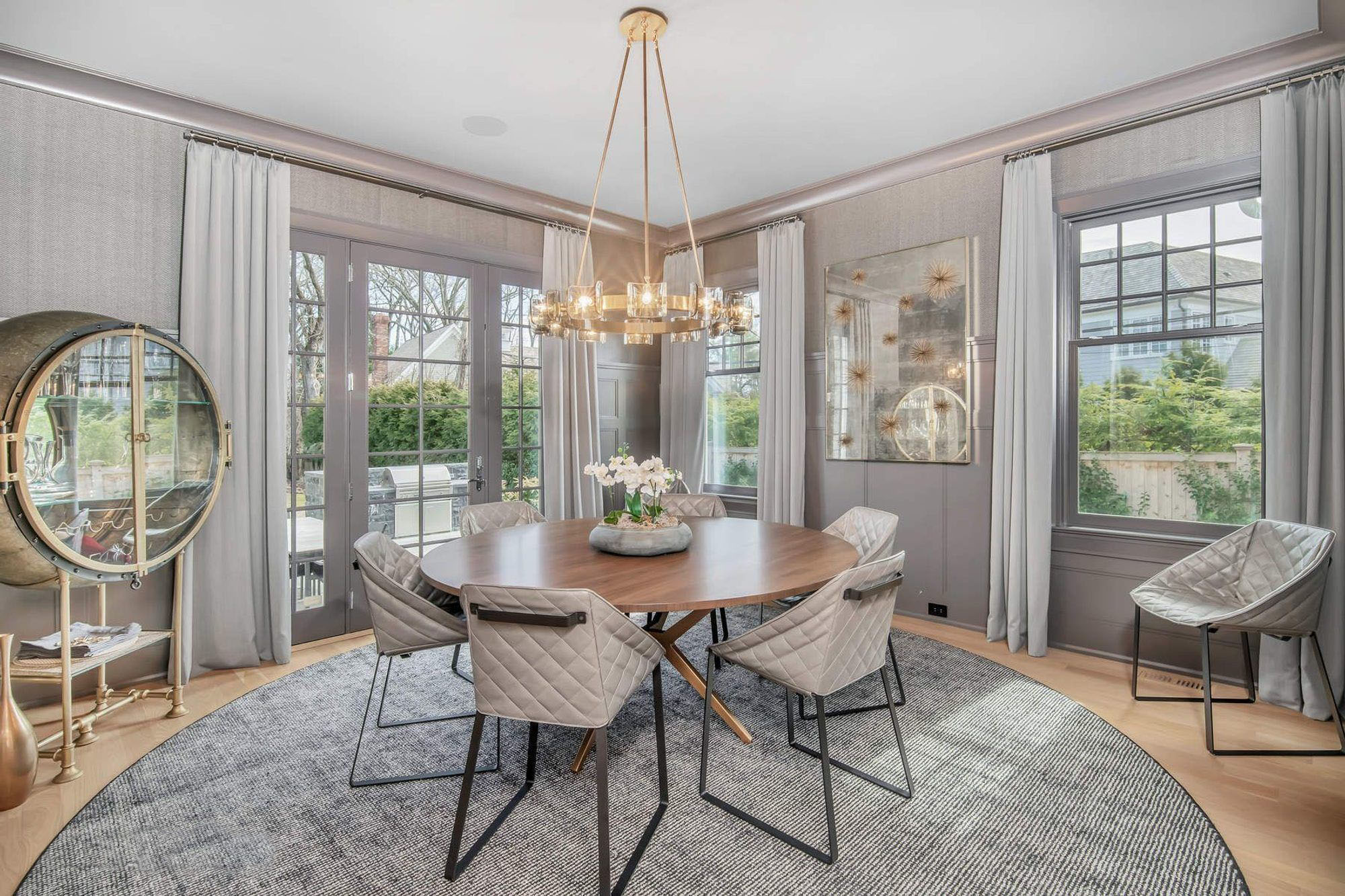 gray monochromatic dining room with wall paneling and wall paper