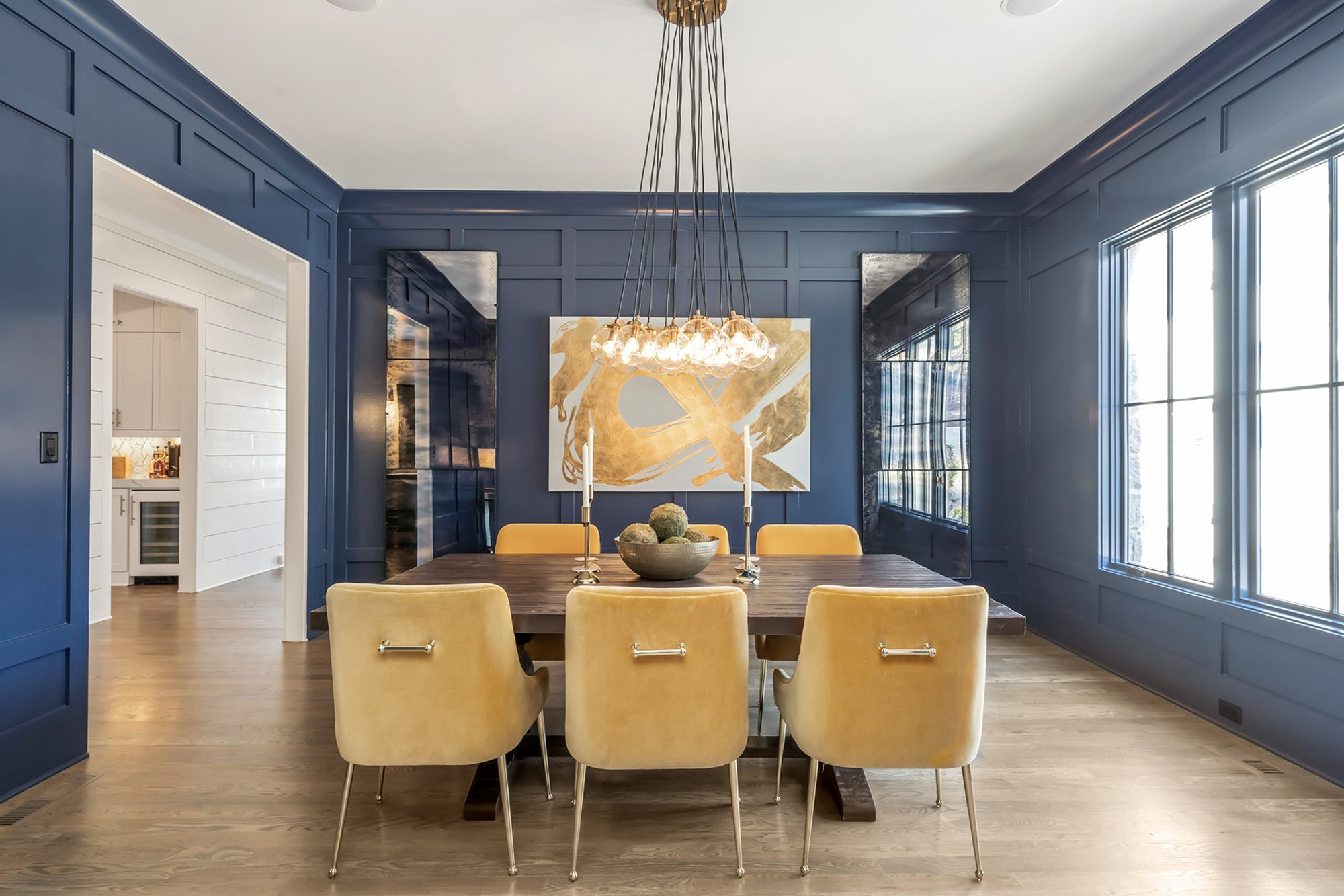 monochromatic dining room color scheme with blue walls & wood dining table and gold chairs wall paneling