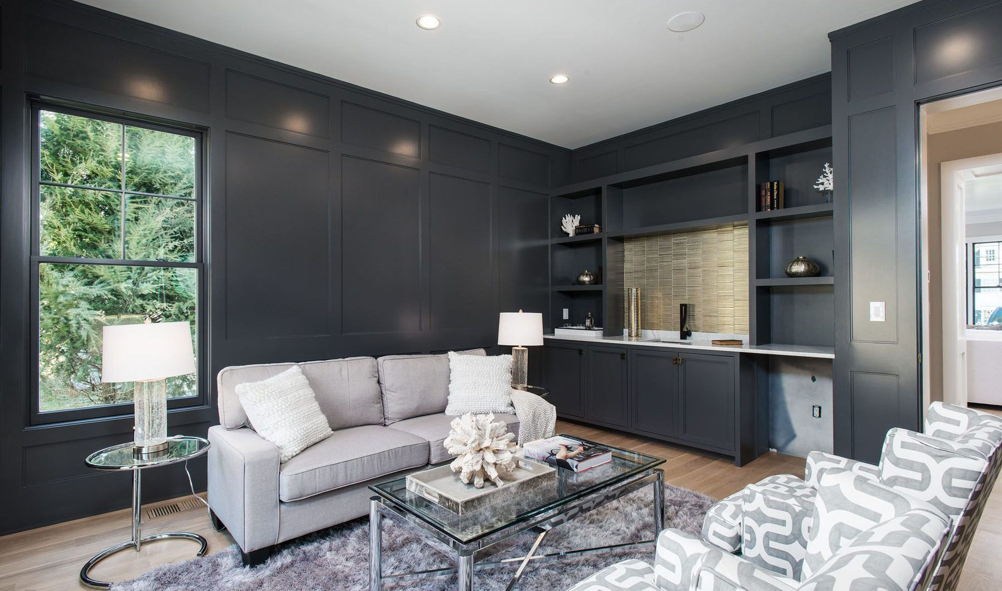 Gray sitting room with wall paneling and built ins which include a wet bar.
