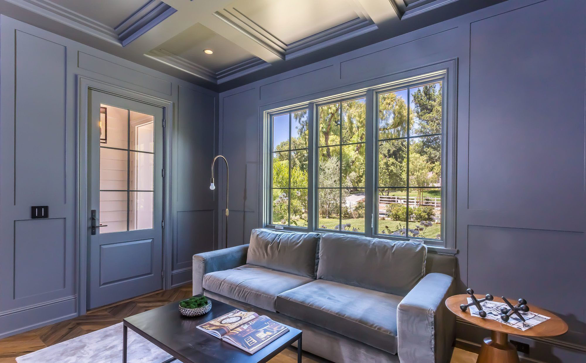 Blue monochromatic sitting room with matching blue coffered ceiling.