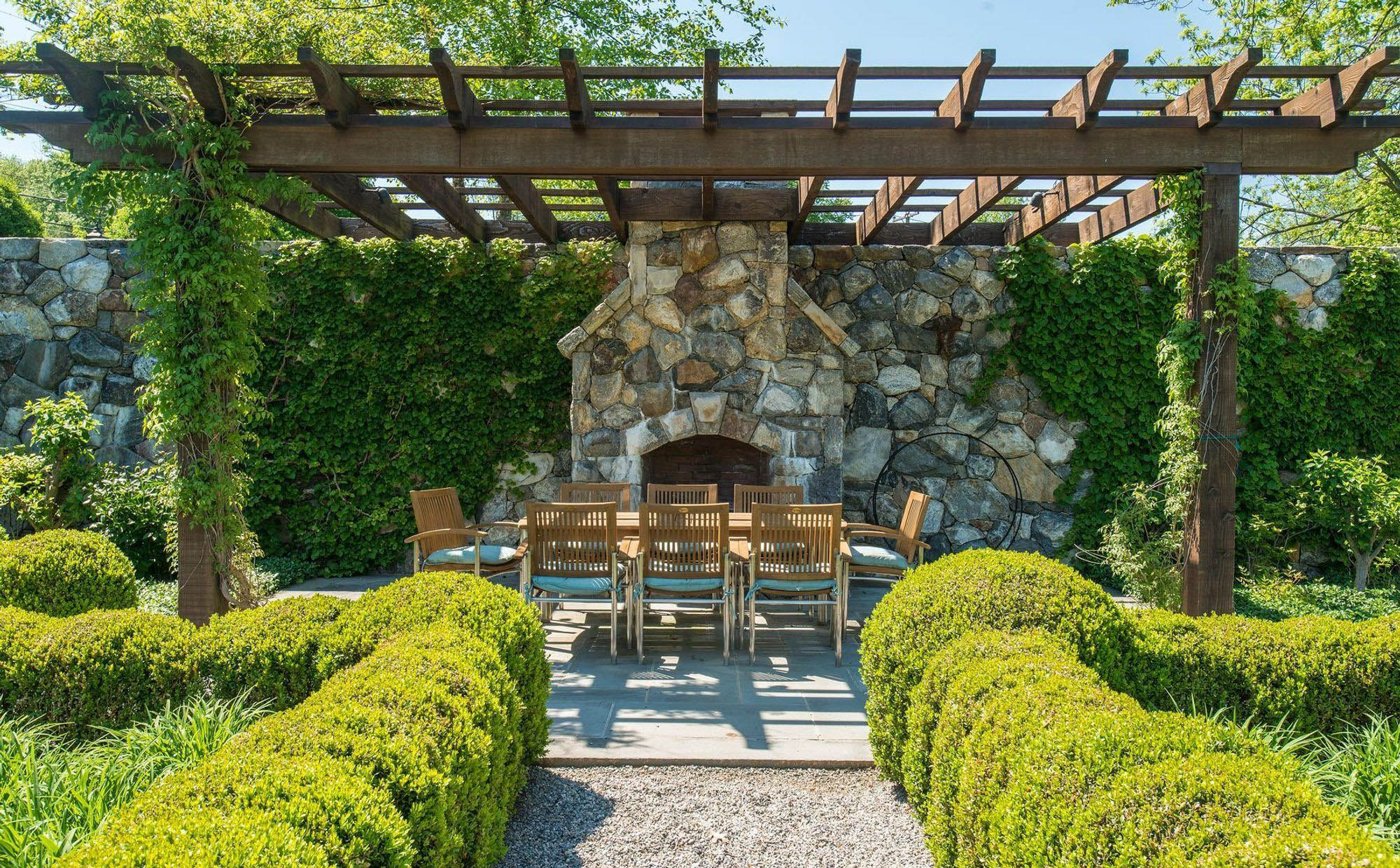 rustic patio furniture set with real wood trellis and ivy stone wall and outdoor fireplace