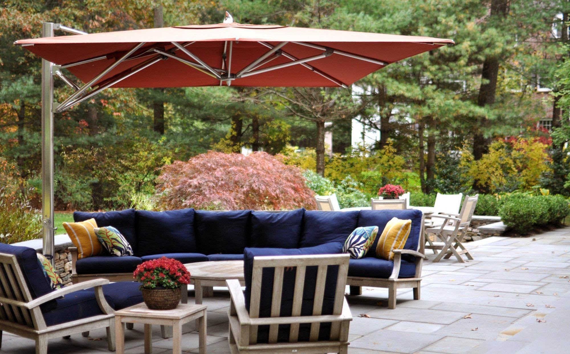 Outdoor patio furniture set with table, chairs, sofa and umbrella. Wood furniture with navy blue cushions. Colorful throw pillows.