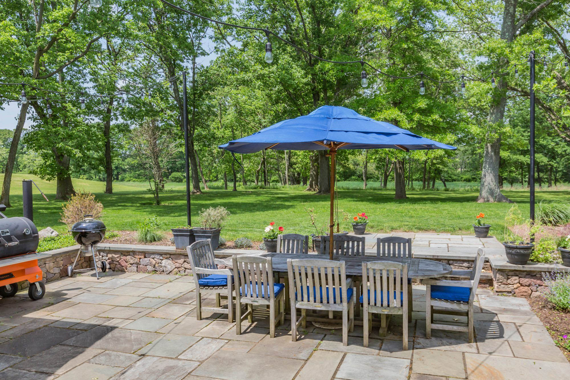 blue outdoor wooden dining table with matching blue seat cushions