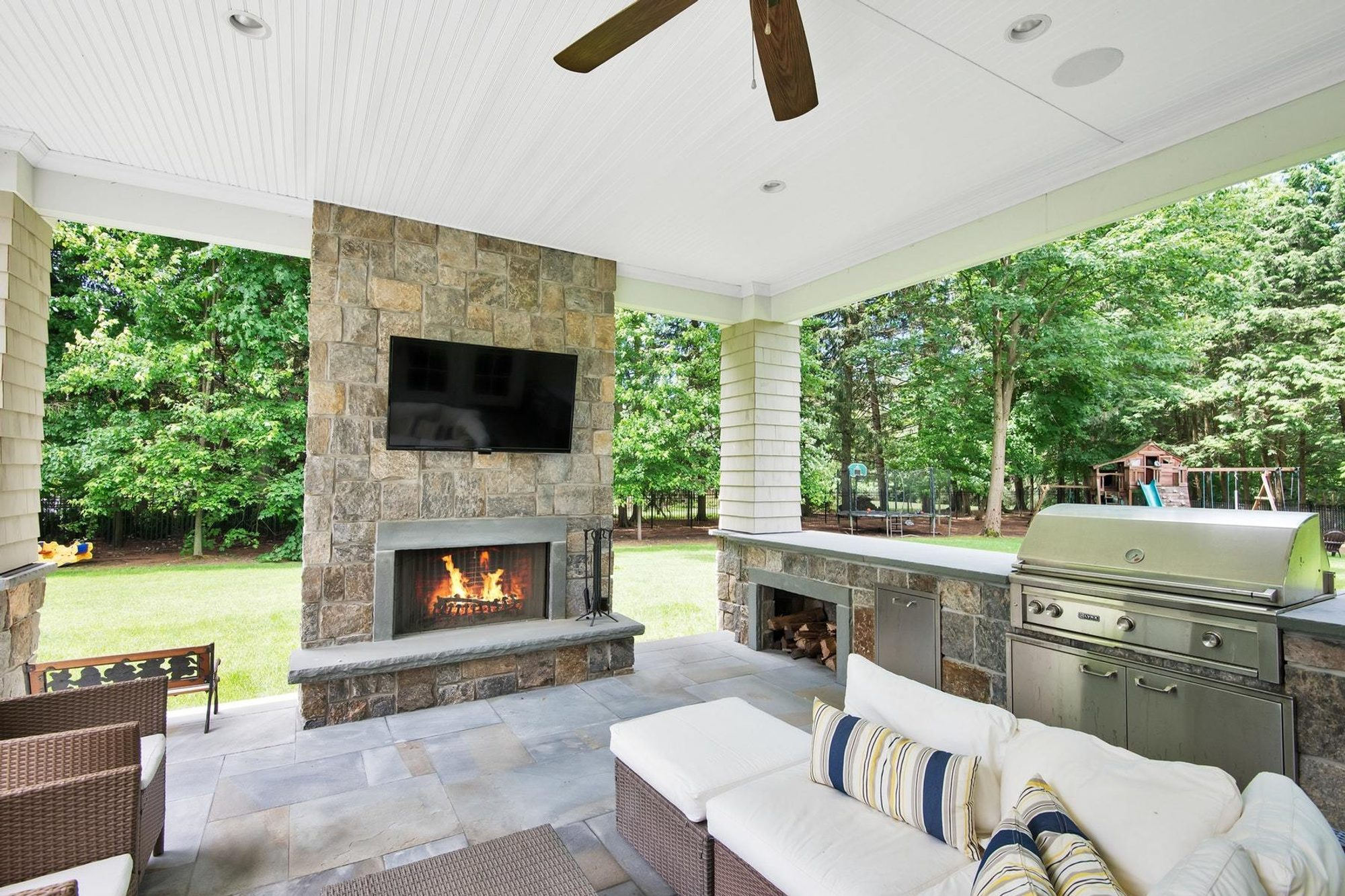 covered patio with wicker furniture and outdoor cushions, outdoor fireplace and kitchen.