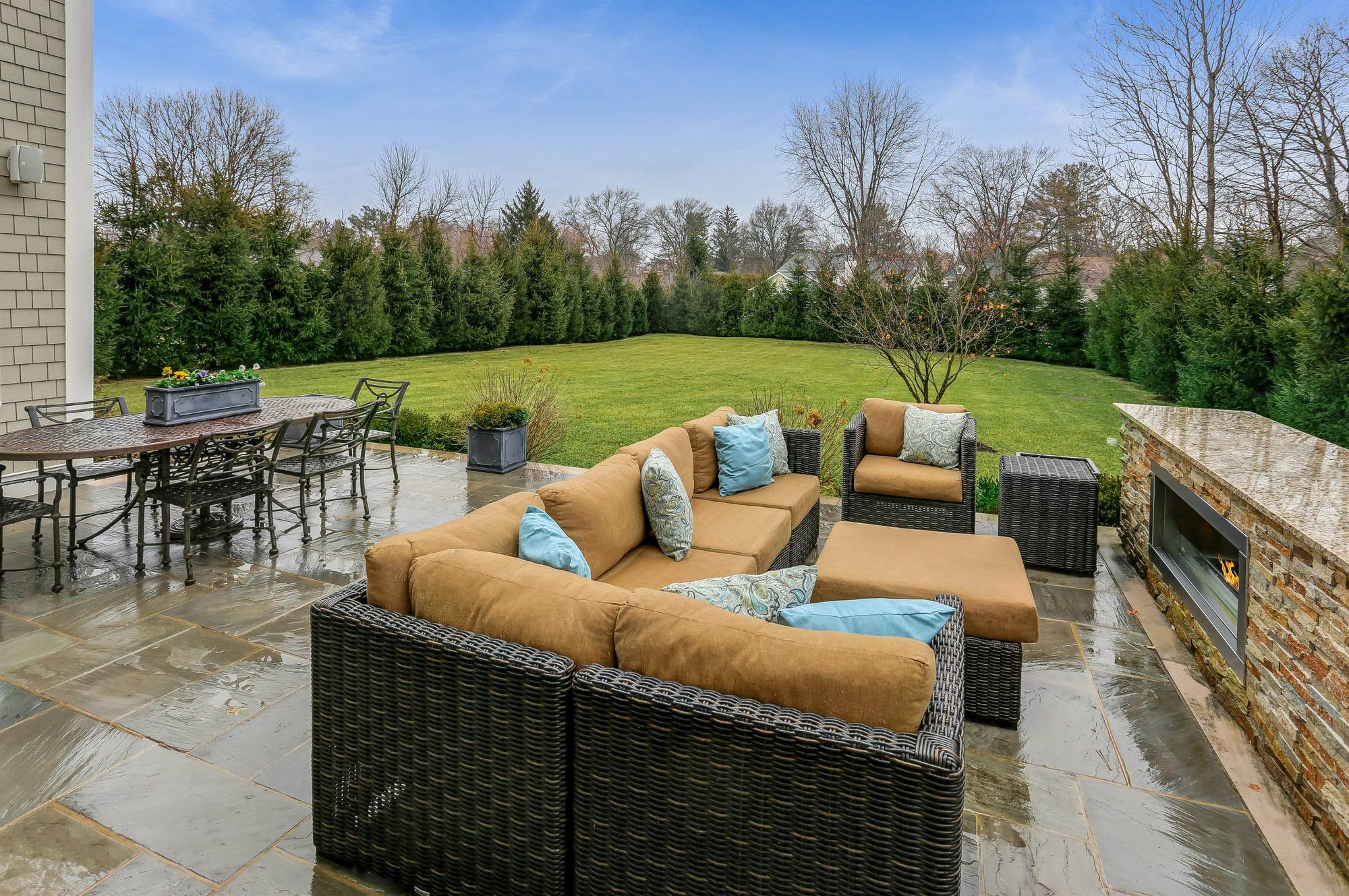 black wicker patio furniture set with brown cushions and blue throw pillows.