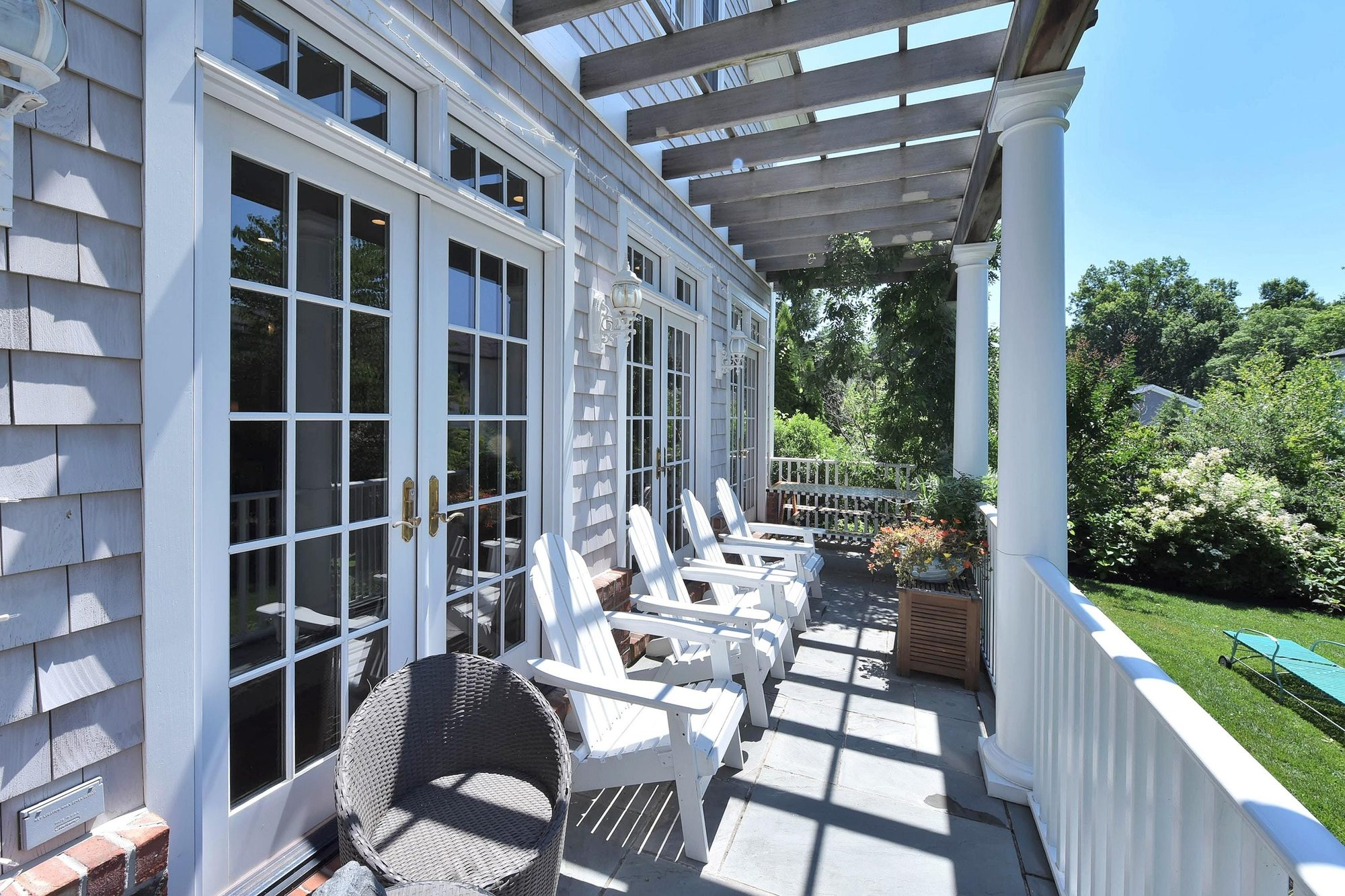 painted outdoor furniture ideas. white painted folding patio chairs on a back patio with arbor.