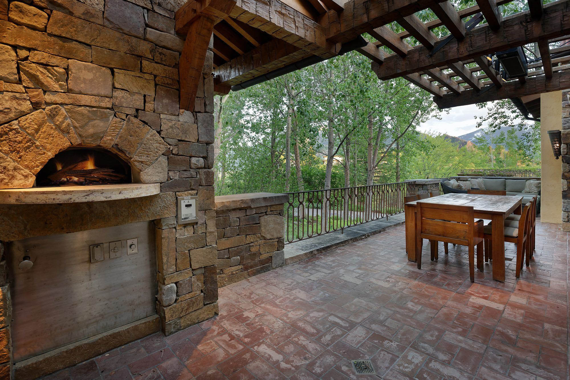 rustic patio furniture ideas real stone, red brick paver floor, iron railings, real timber pergola