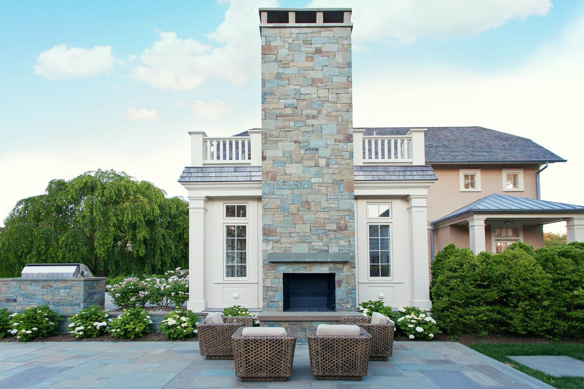 beautiful small wicker patio furniture set in front of a gas fireplace with stunning real stone chimney and blue stone patio