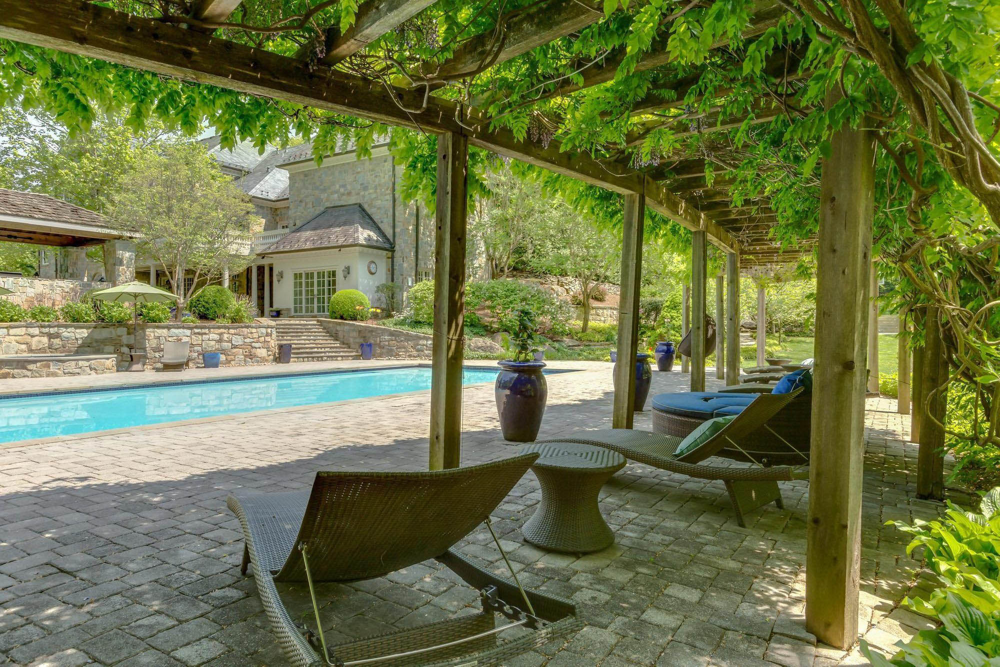 rustic poolside furniture trellis with overgrown ivy poolside wicker chairs & table blue cushions.