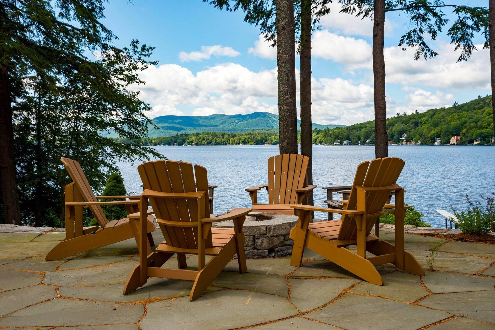 Simple outdoor patio furniture. Wood chairs around a stone fire pit with a fantastic water view.