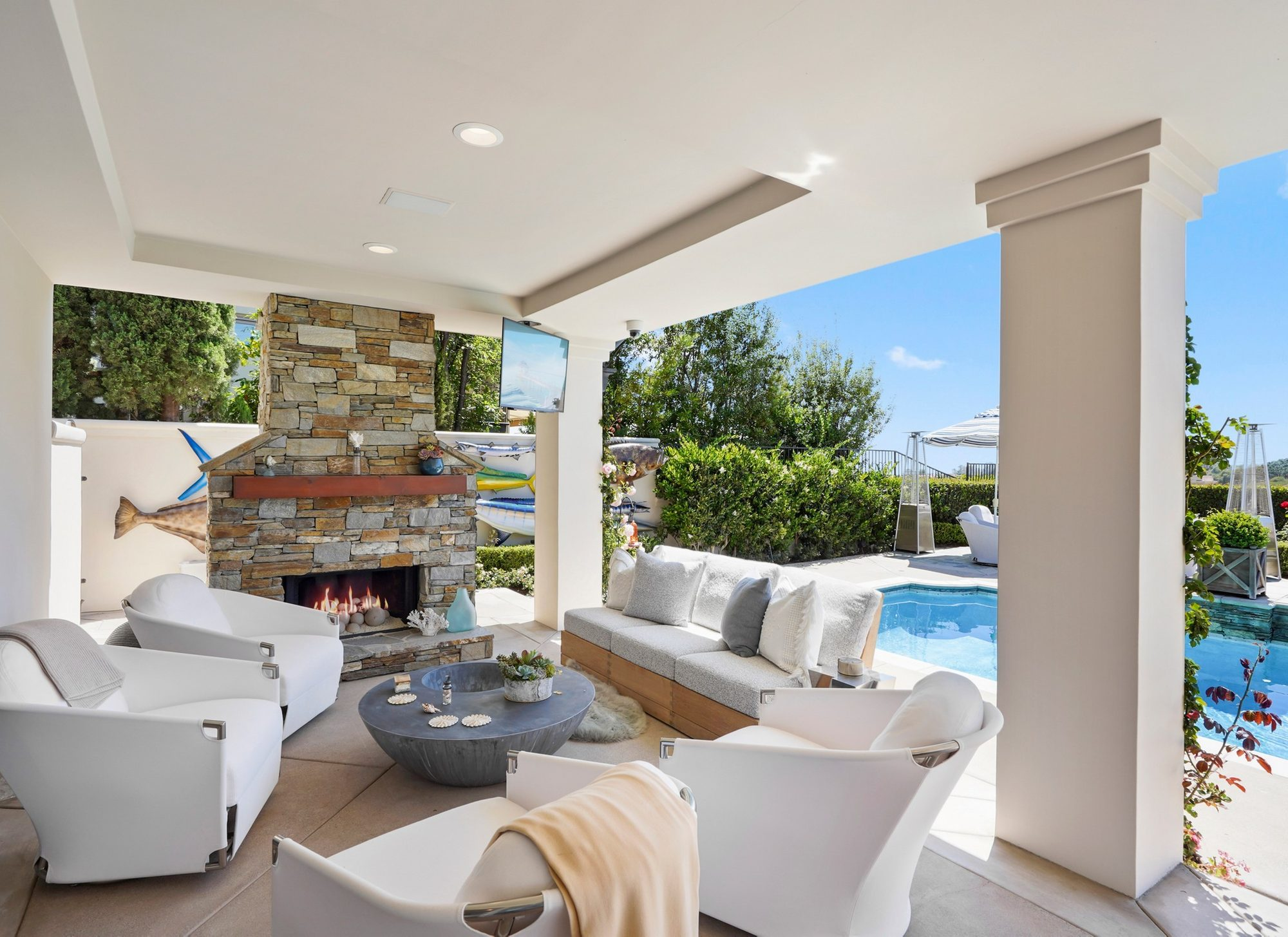 Beautiful poolside covered patio with outdoor furniture set and built in gas fireplace.