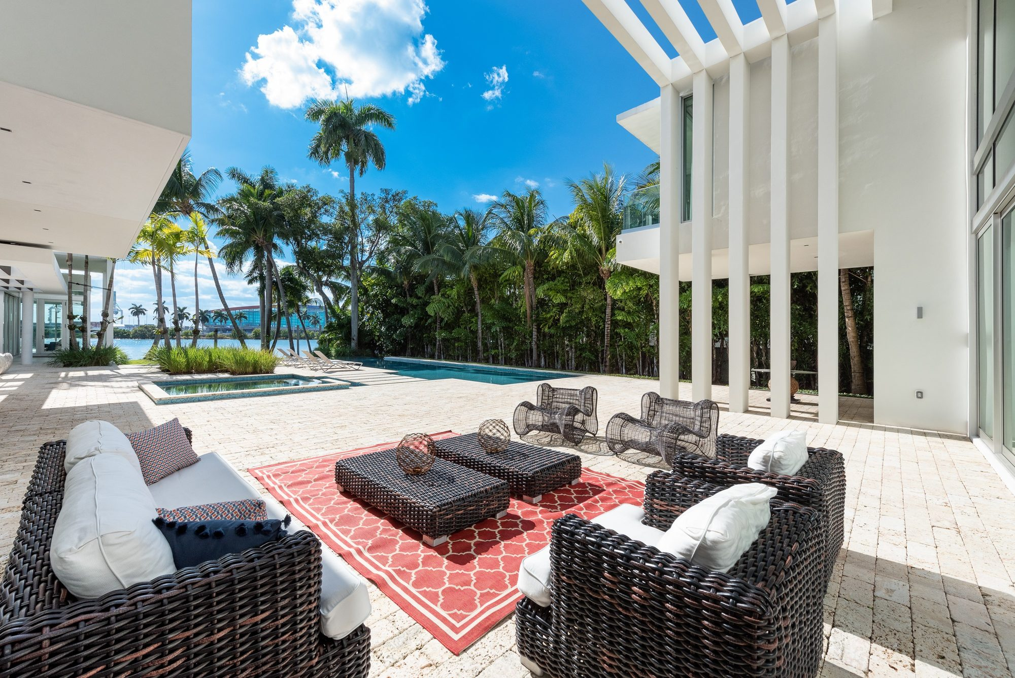 Woven dark brown patio set with a modern vibe. White cushions, coffee tables and colorful throw pillows capped off by a stylish red outdoor area rug.