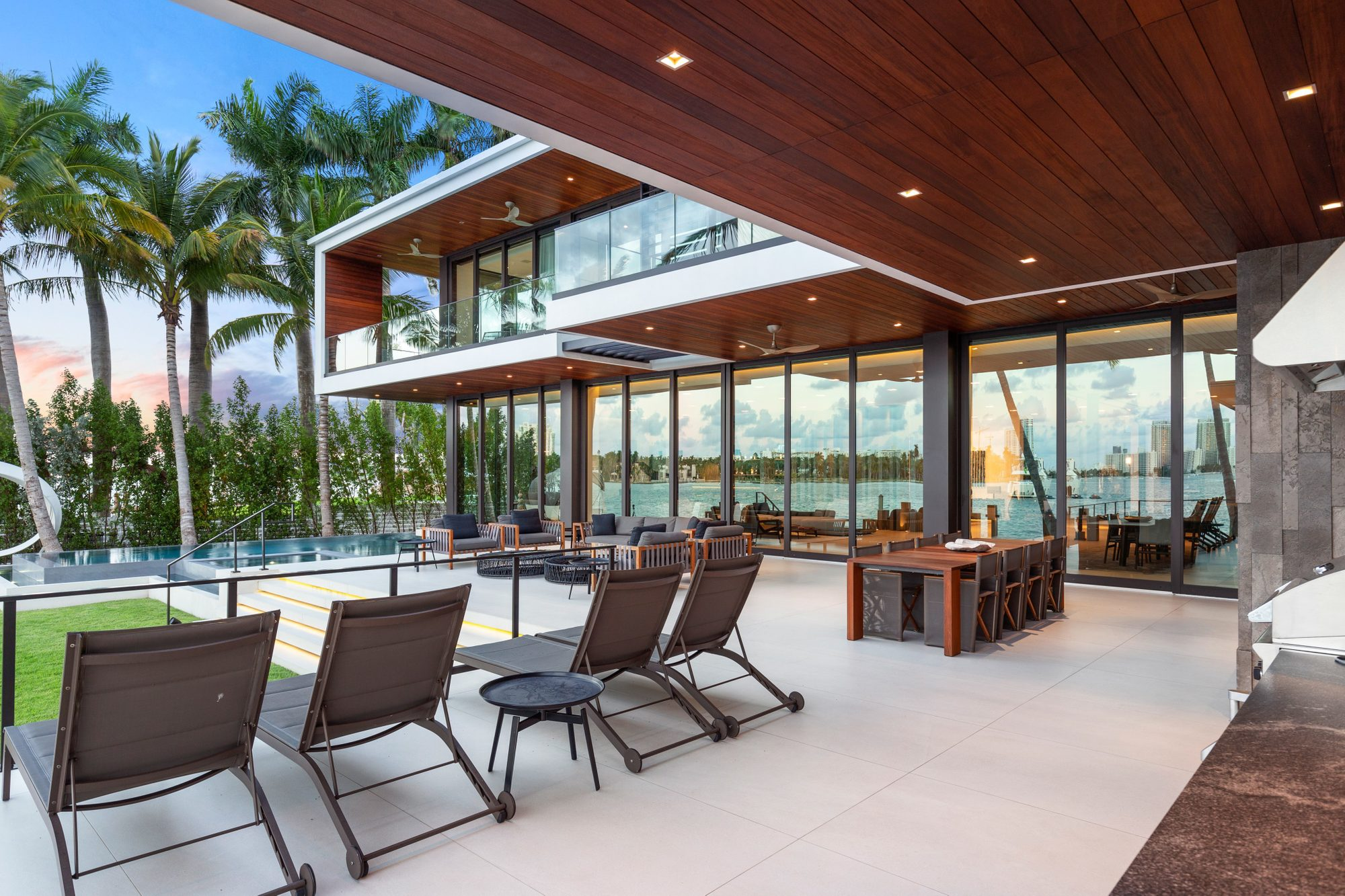 Matching gray and wood modern outdoor furniture sets sectioned off into 3 distinct areas. Suntanning, lounging and dining.