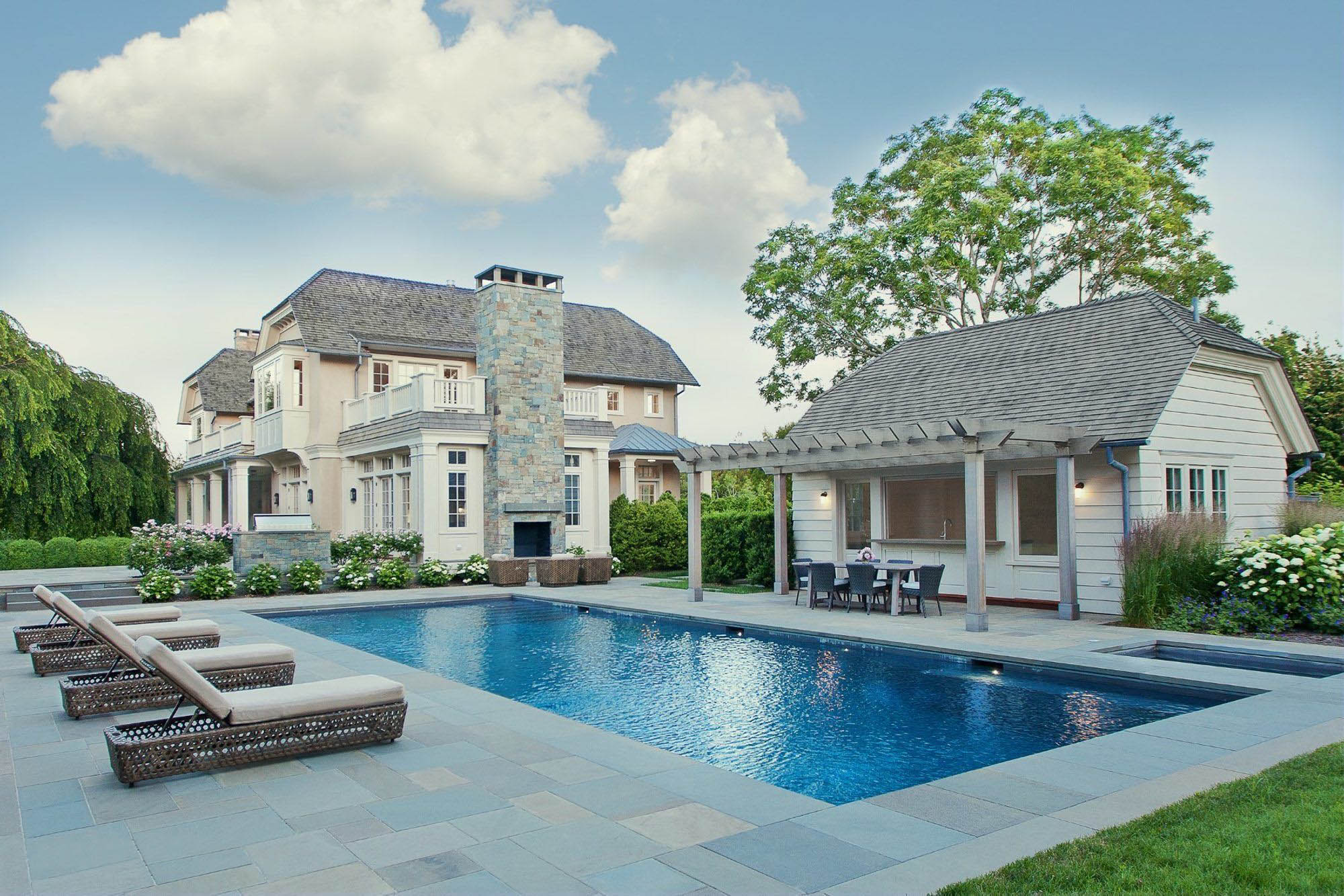 Blue stone pool patio with lounge woven furniture and seating areas. Pool house with arbor.