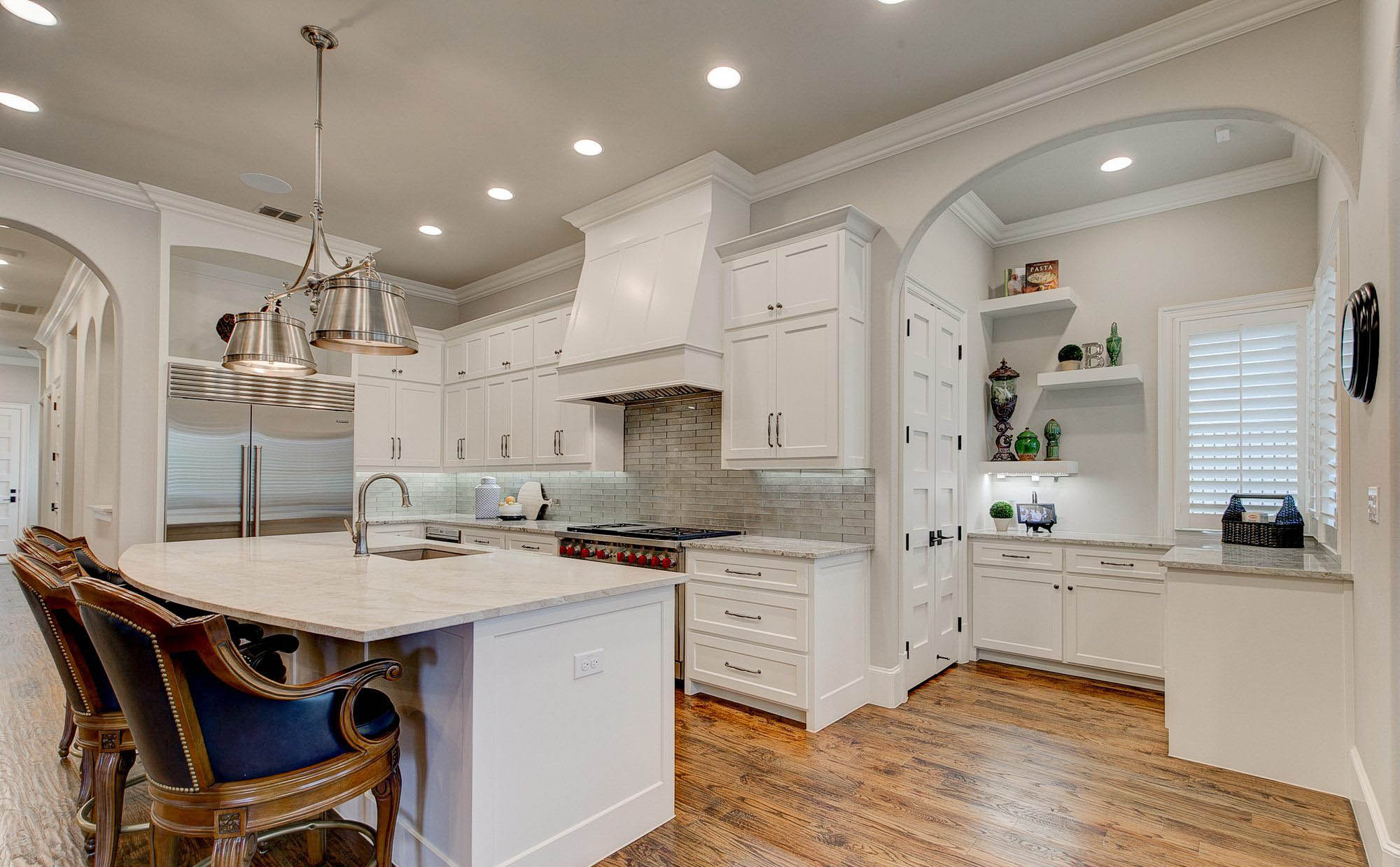 White granite with white marble quartz kitchen countertops and white cabinets. Rustic hardwood floors.