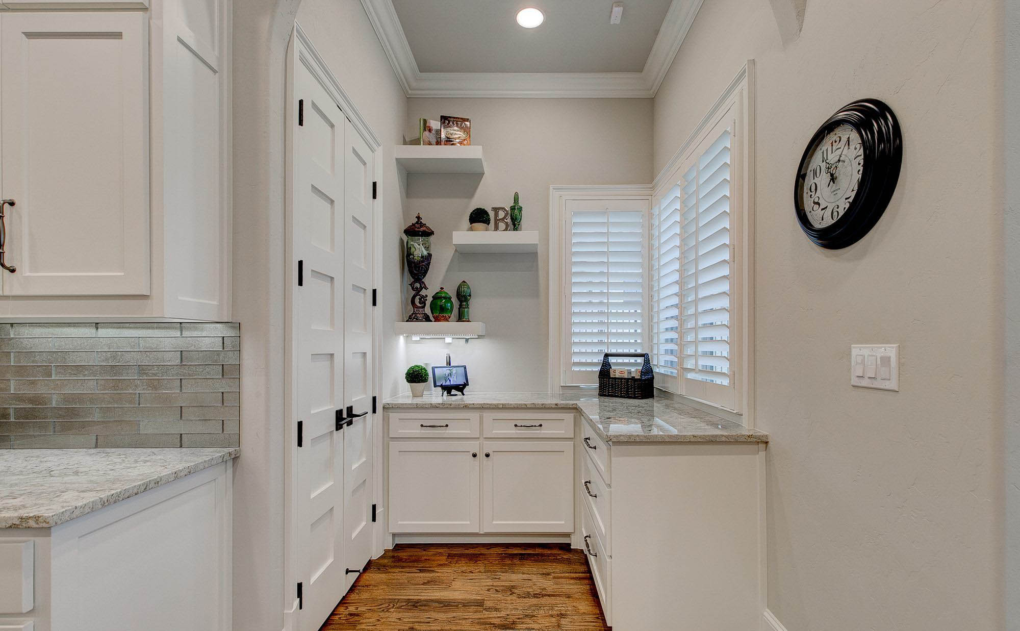 White granite pantry countertops with white cabinets. Hardwood flooring. quartz vs granite.
