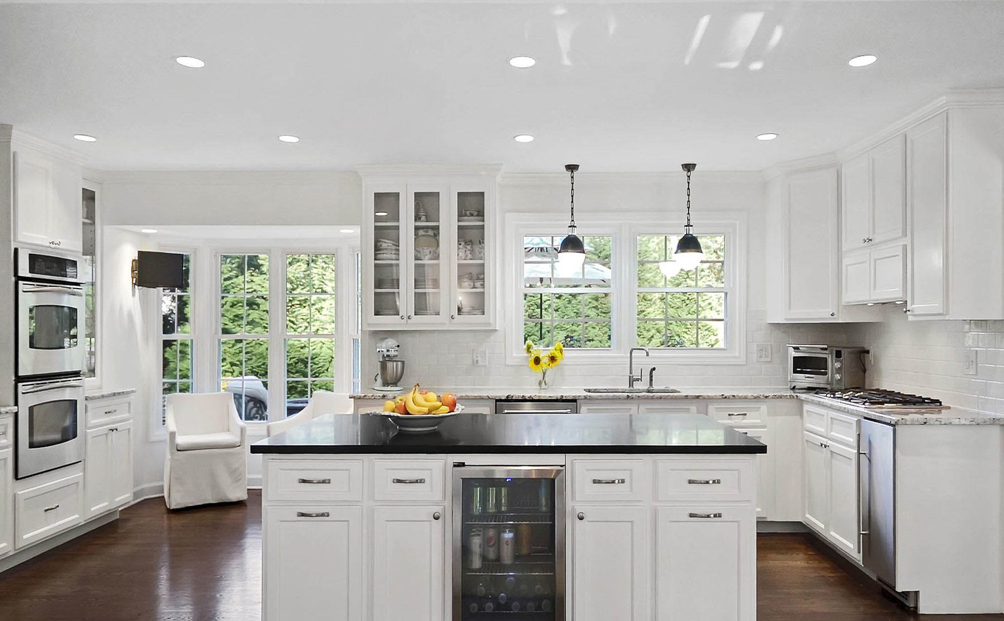White granite and black quartz countertops with white cabinets and subway tile backsplash.