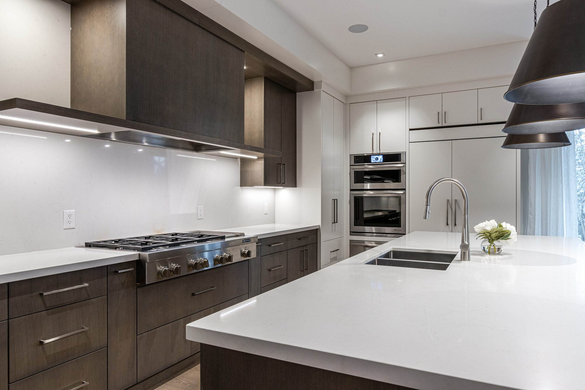 Modern kitchen featuring flat faced muted brown and white cabinets with white quartz countertops. Solid slab white quartz backsplash.