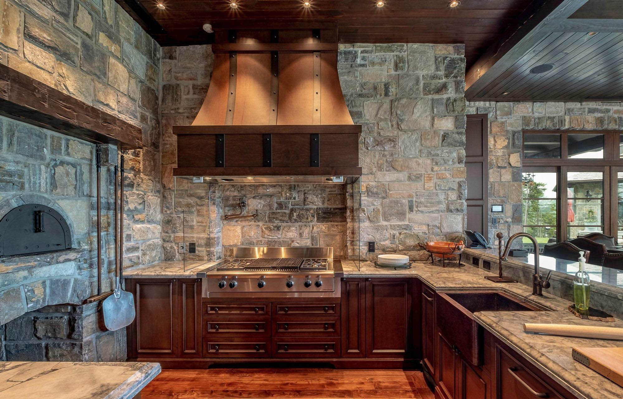 Rustic kitchen design with cream colored granite countertops. Built in stone pizza oven.