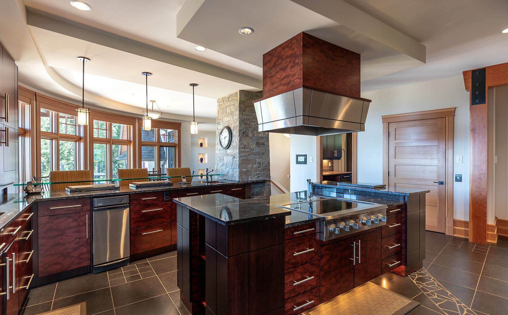 Modern rustic kitchen design with black granite countertops, rich reddish brown cabinets and stainless steel.