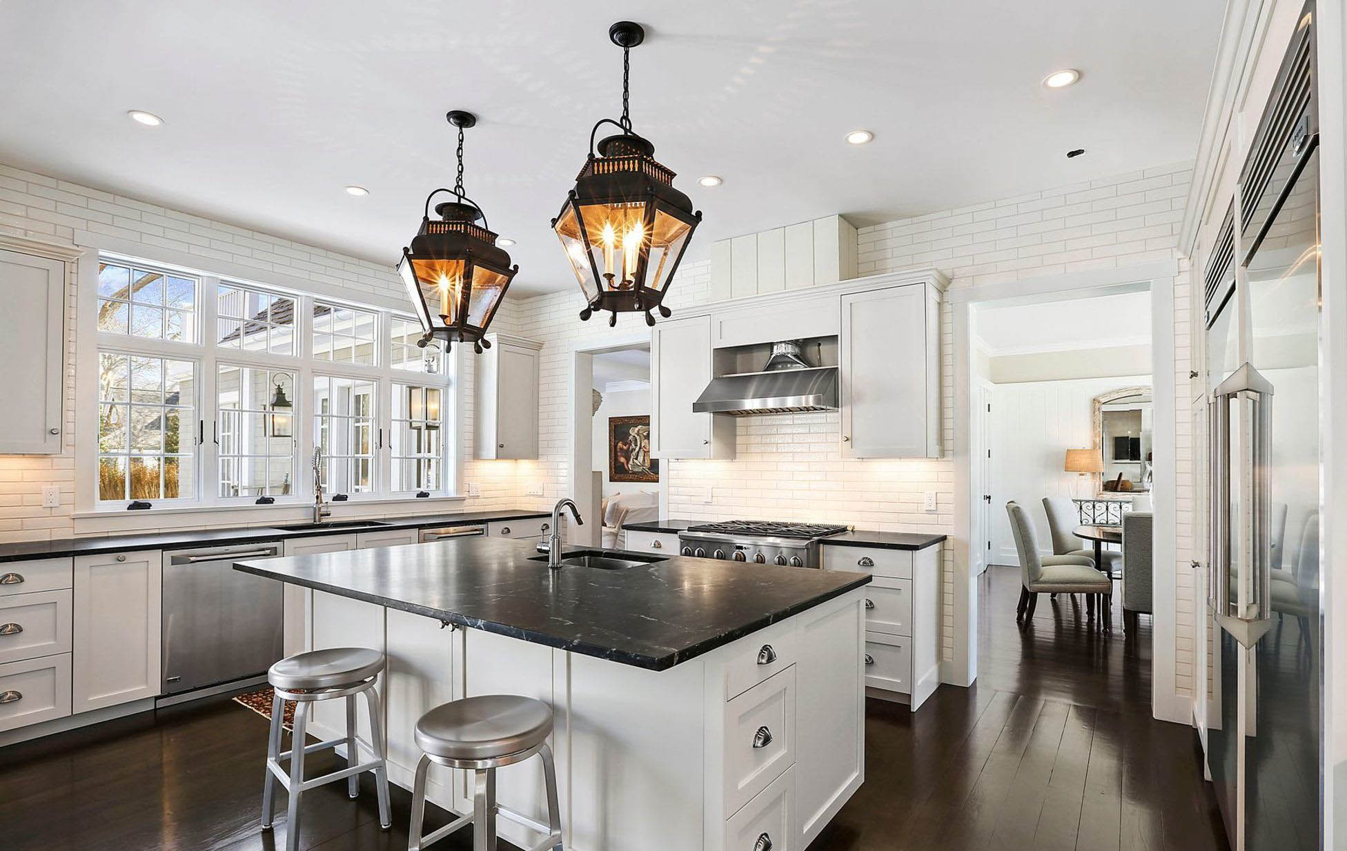 White kitchen cabinets with black granite. Dark brown hardwood floors. Stainless steel appliances. White subway tile backsplash. Quartz vs granite.