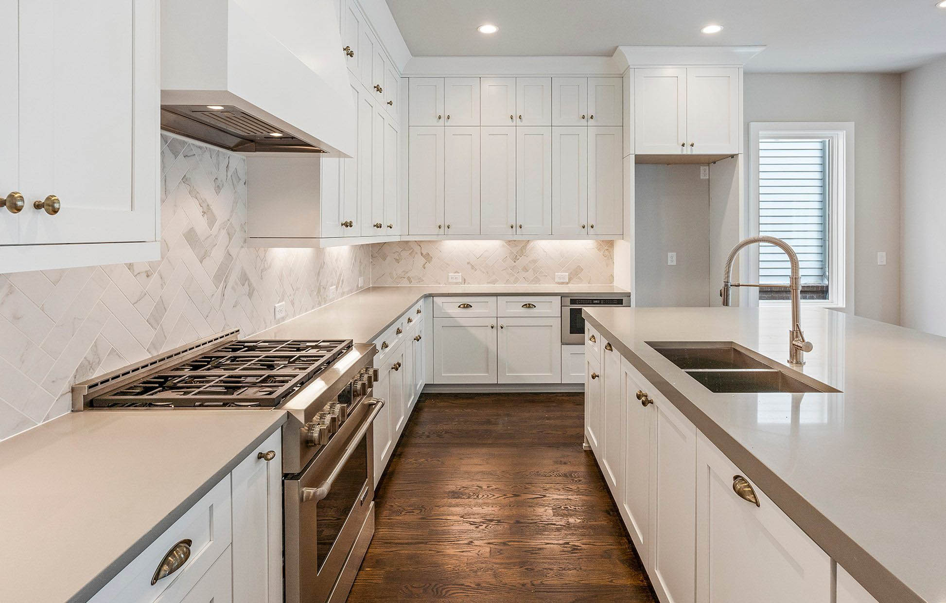 Gray quartz kitchen countertops with white cabinets and porcelain marble backsplash. Stainless steel appliances and rustic hardwood floors.