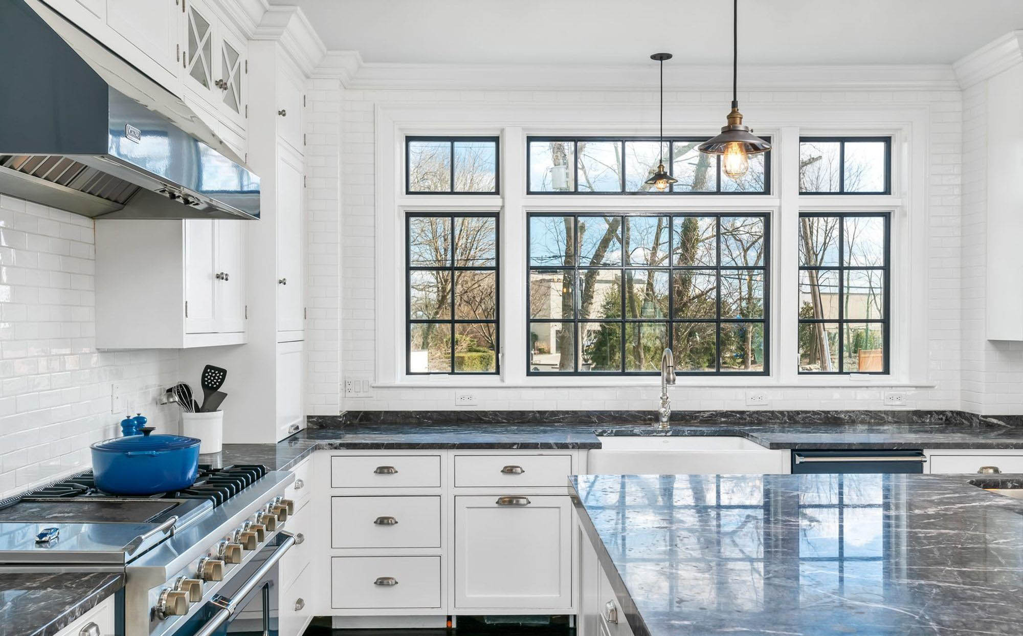 Black and white kitchen design. White cabinets with black granite. Black frame windows with white trim and white subway wall tiles.