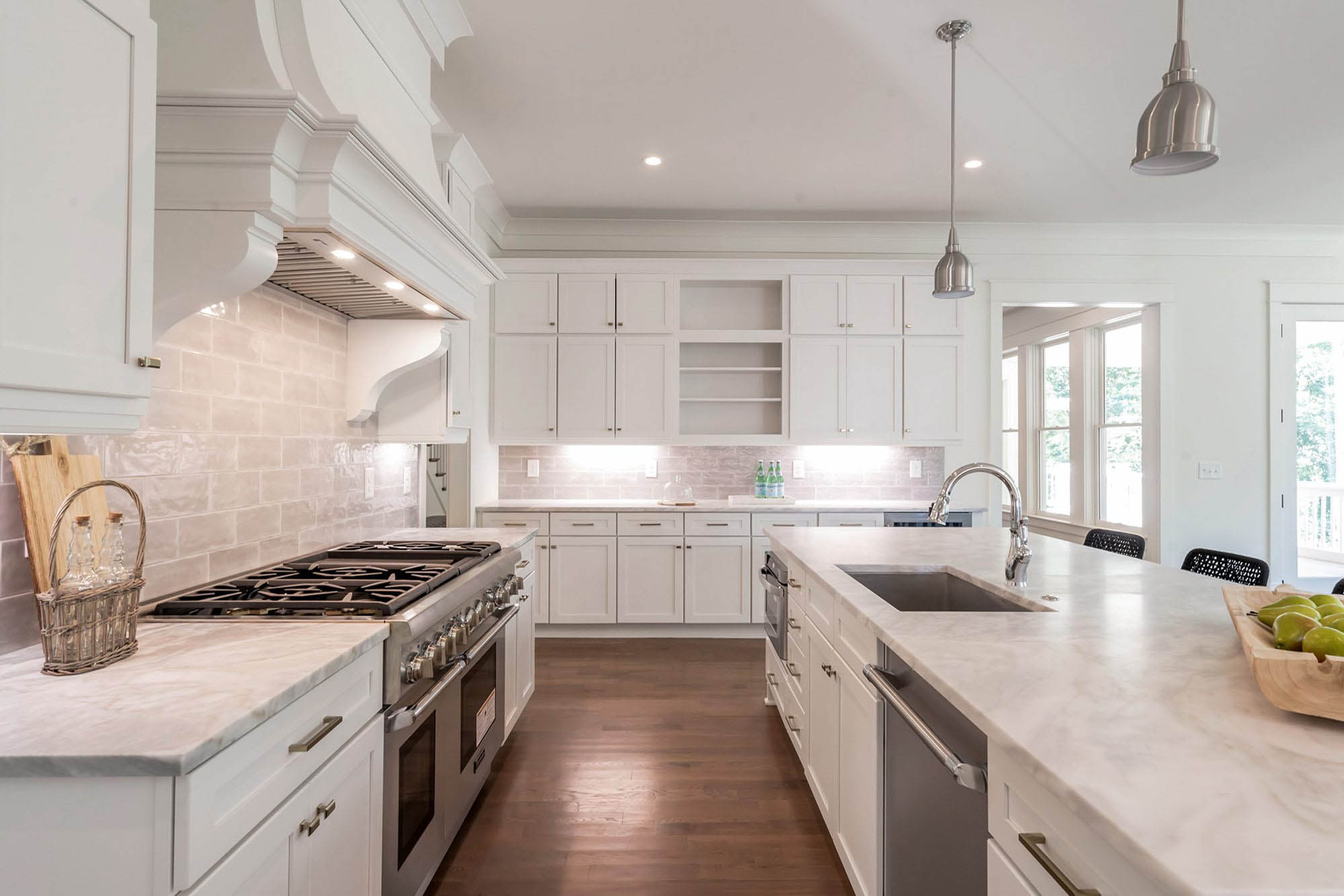 Marble quartz kitchen countertops with white cabinets and hardwood floors. Gray tile backsplash. quartz vs granite.