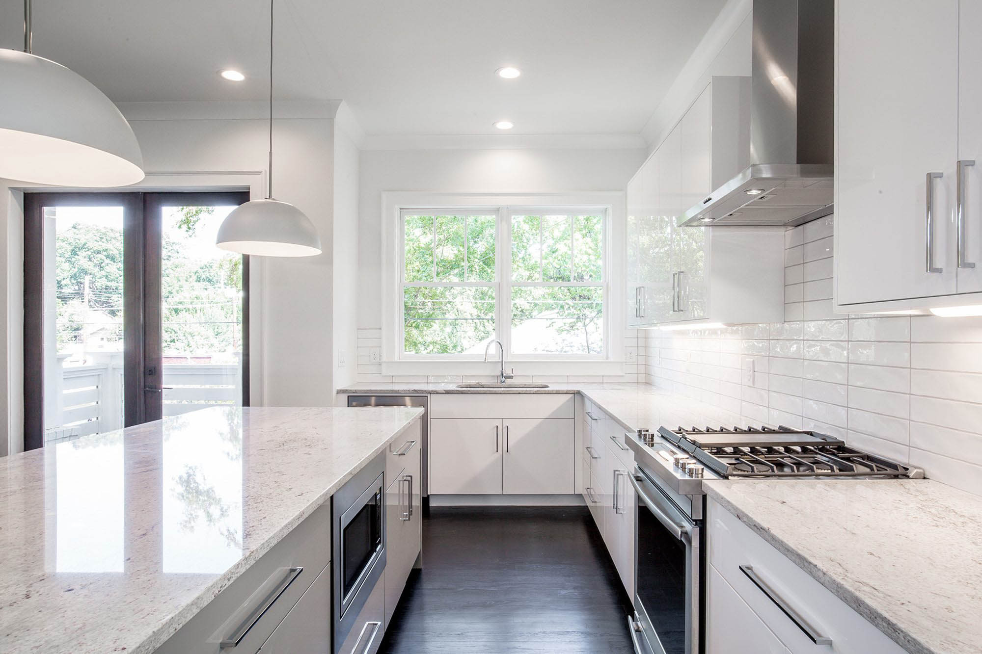 White quartz with spotted gray and brown highlights throughout. A very white kitchen design.