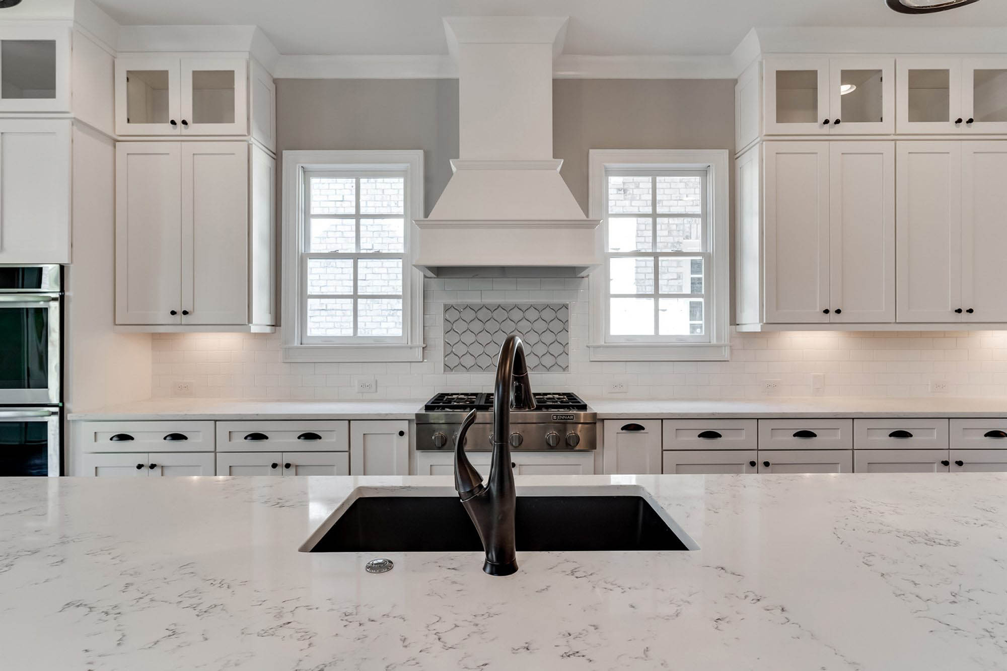 White marble quartz countertop with white cabinets and backsplash. Bronze faucet and sink.