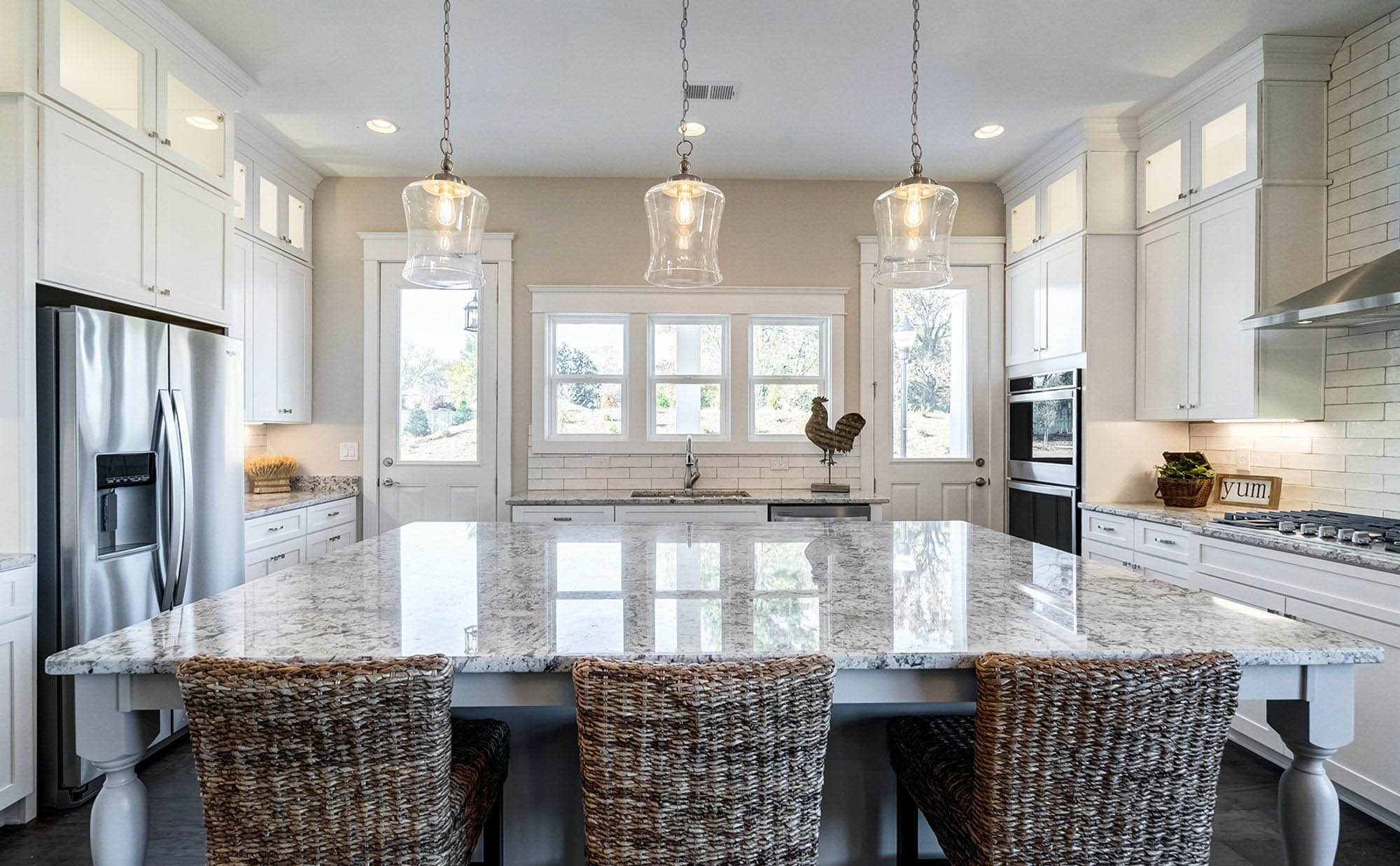 White granite kitchen countertop with brown  and gold. Large center island with wicker seating.