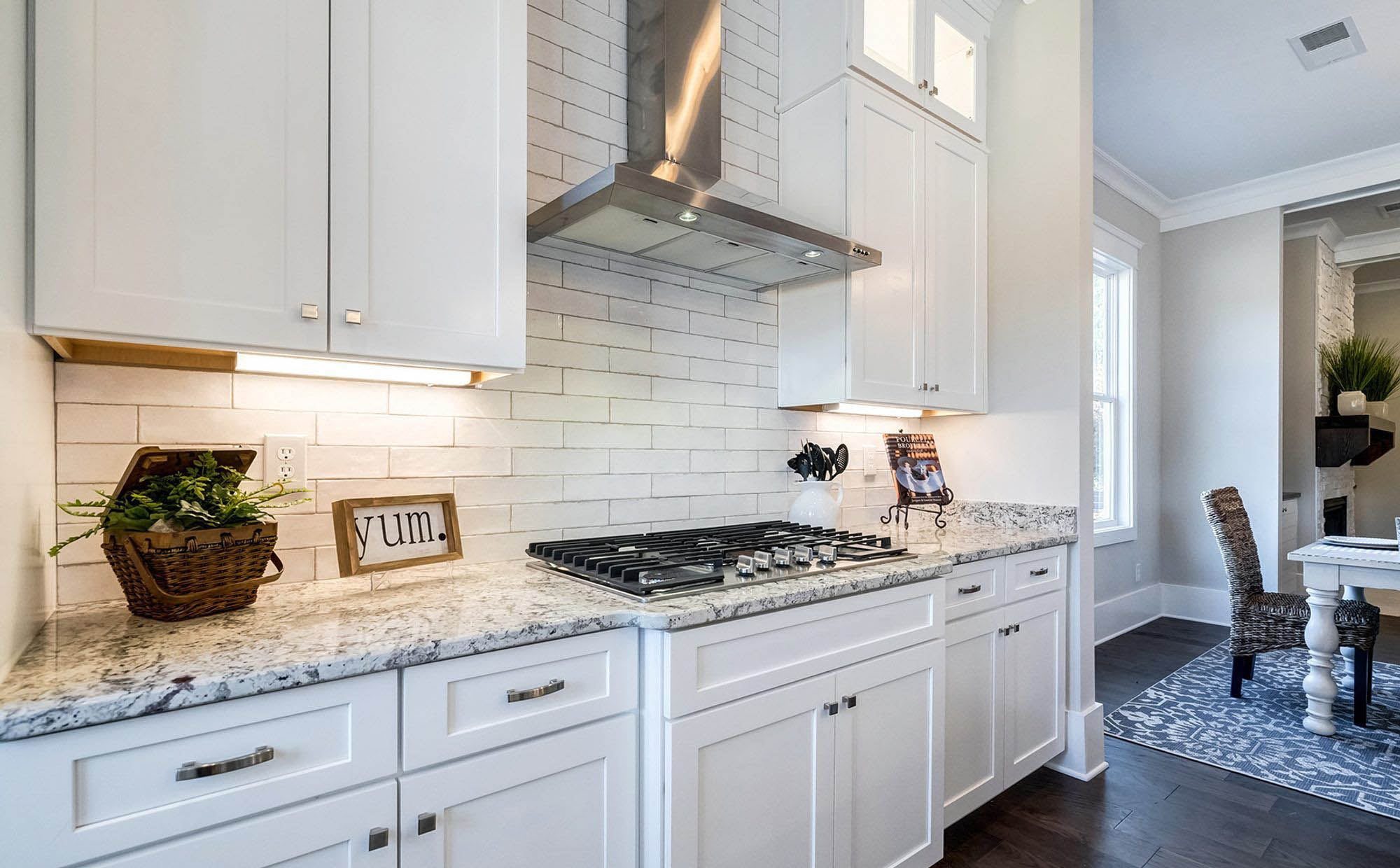 More white granite kitchen countertops with gold and brown. White subway tile backsplash with counter decorations.