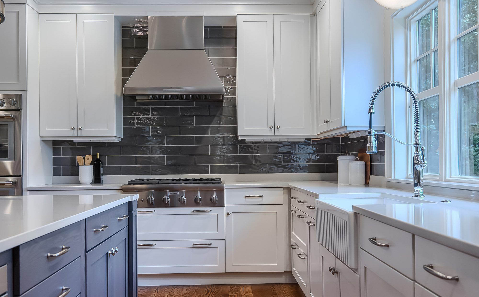 Gray quartz countertops with white cabinets and blue center island. Dark gray subway backsplash tiles.
