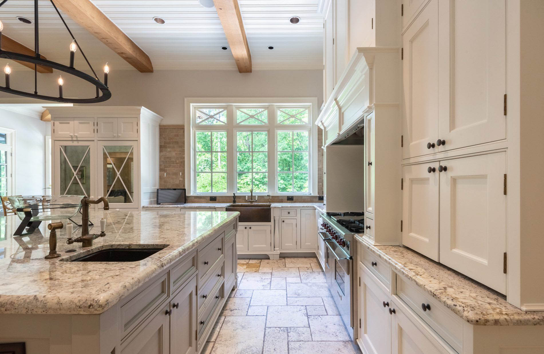 Cream kitchen cabinets with cream and brown granite countertops. Natural tan stone flooring tiles and subway backsplash.