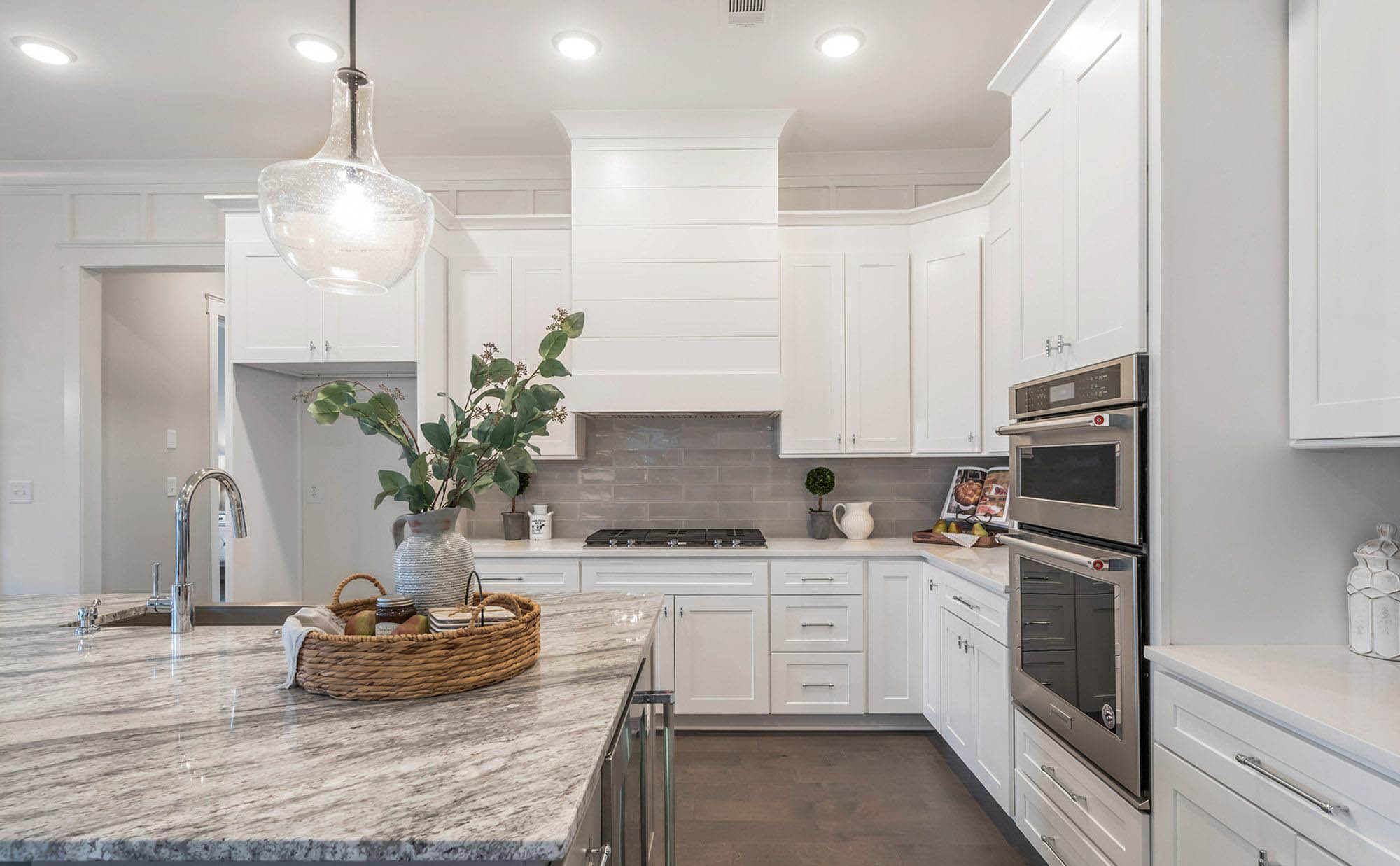 Gray and white granite countertops with white shaker style cabinets and a light gray subway backsplash tile.