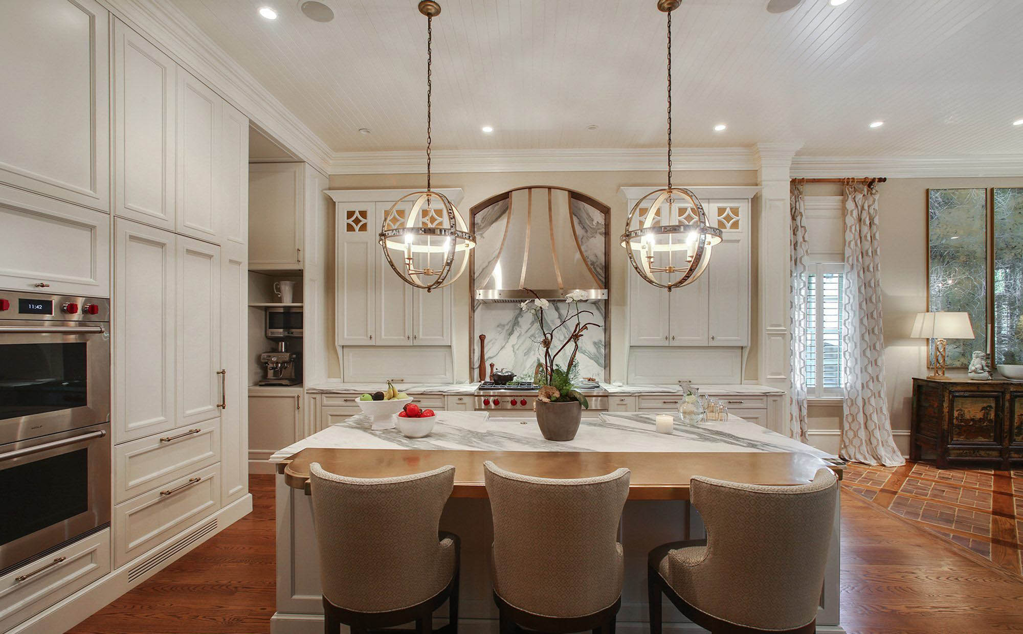 Warm cream kitchen cabinets with marble quartz center island and rich hardwood floors.